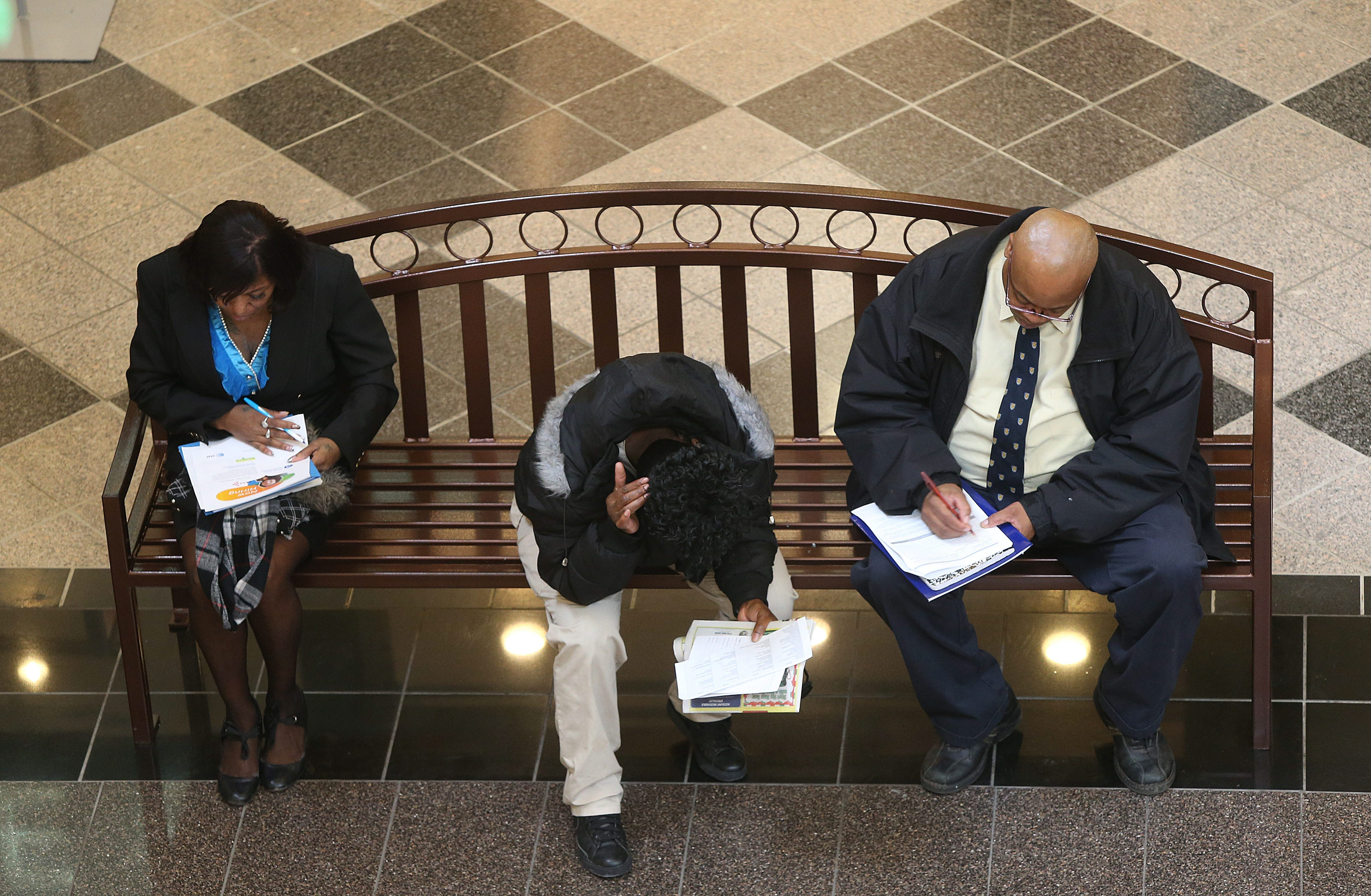 Job-seekers fille out job applications at a job fair at the Walden Galleria earlier this year. (News file photo)