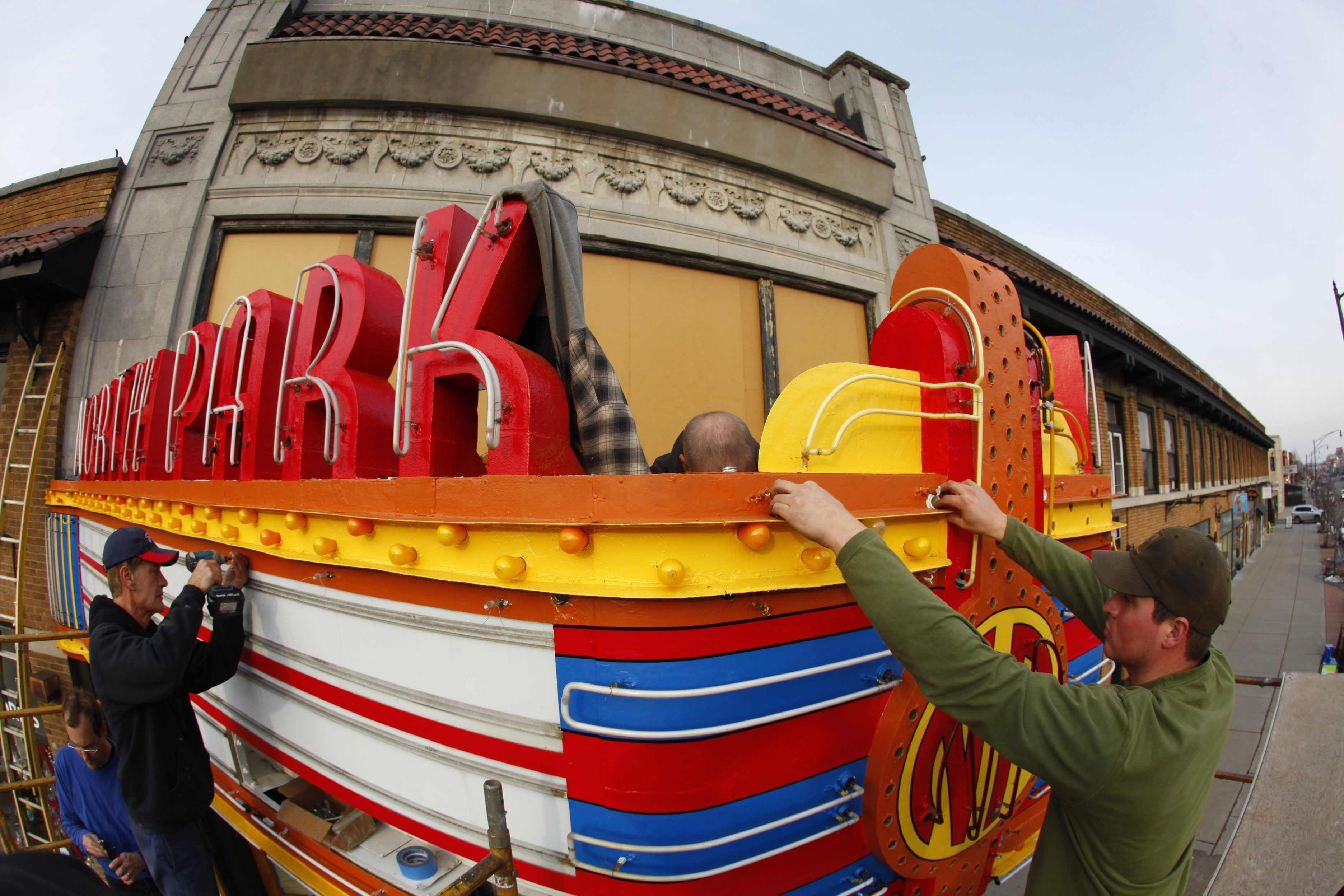 Mike Golubski, left, and Kevin Ernst from Flexlume install LED lights on the North Park Theatre's iconic marquee.