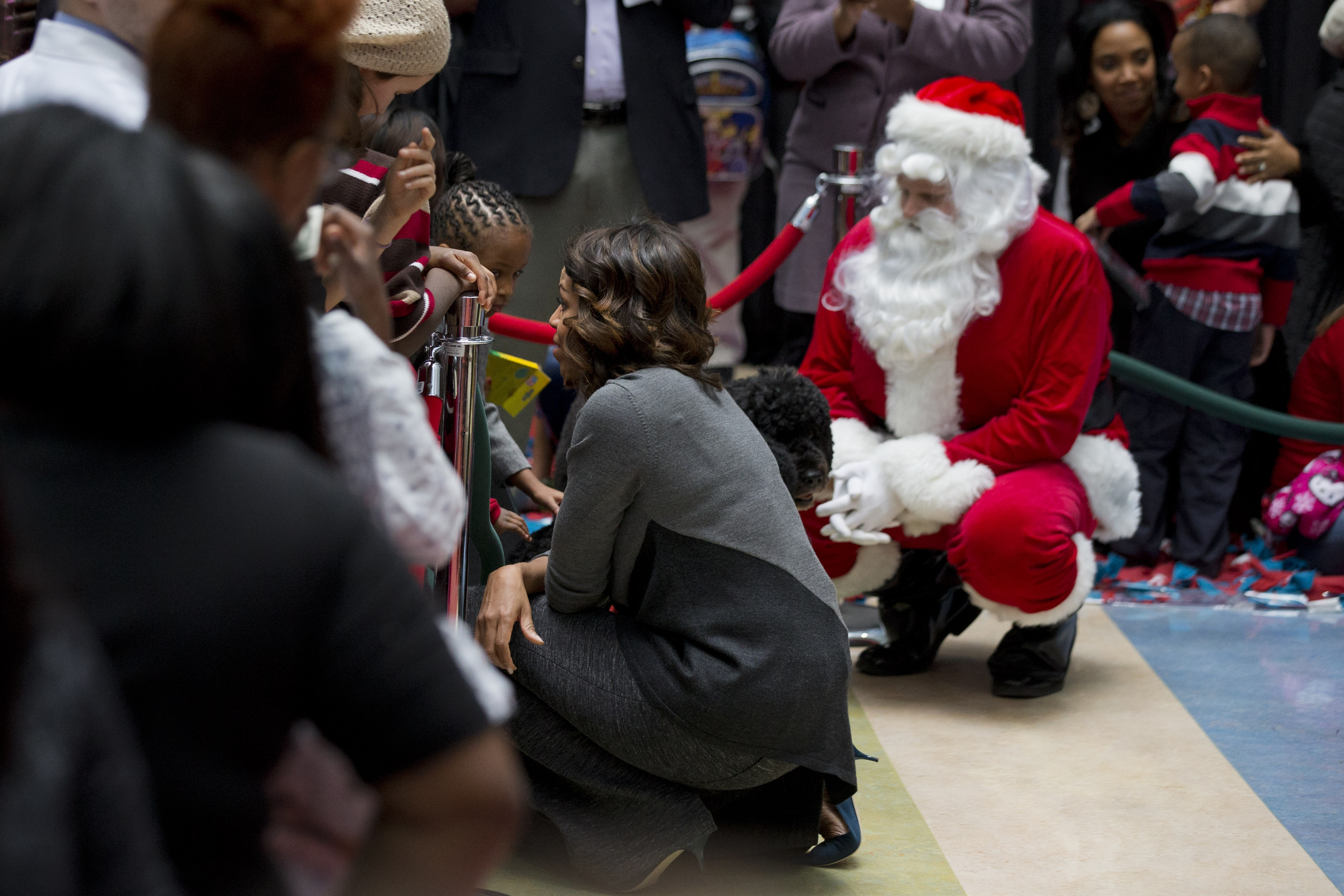 First lady Michelle Obama, foreground, and Santa got down to kids' level after reading them a holiday story at Children's Hospital in Washington on Monday.