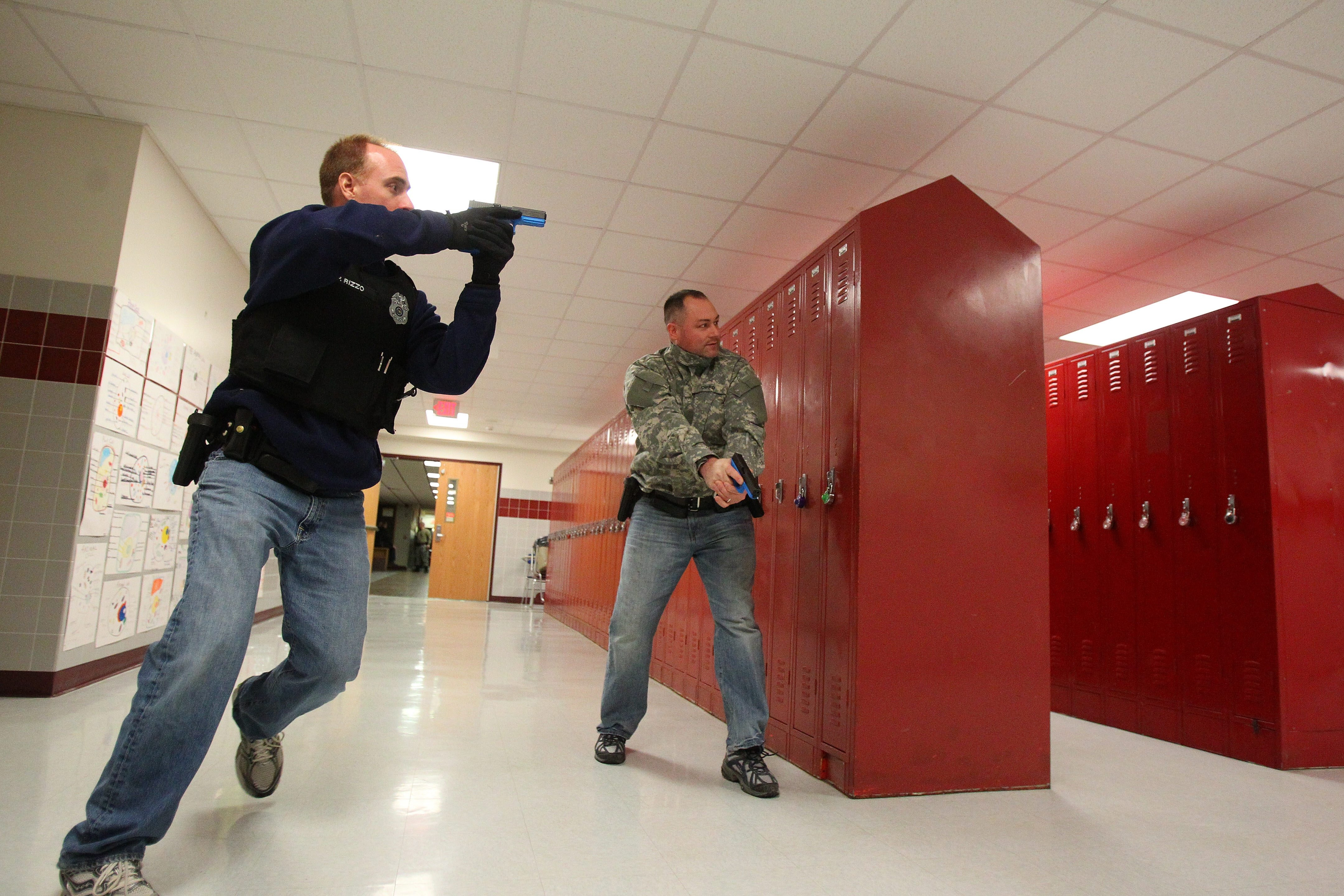 "Orchard Park Police Officers Patrick Rizzo, left, and Daniel Lagoda enter a hallway during an ""active shooter"" drill in Orchard Park High School earlier this month."