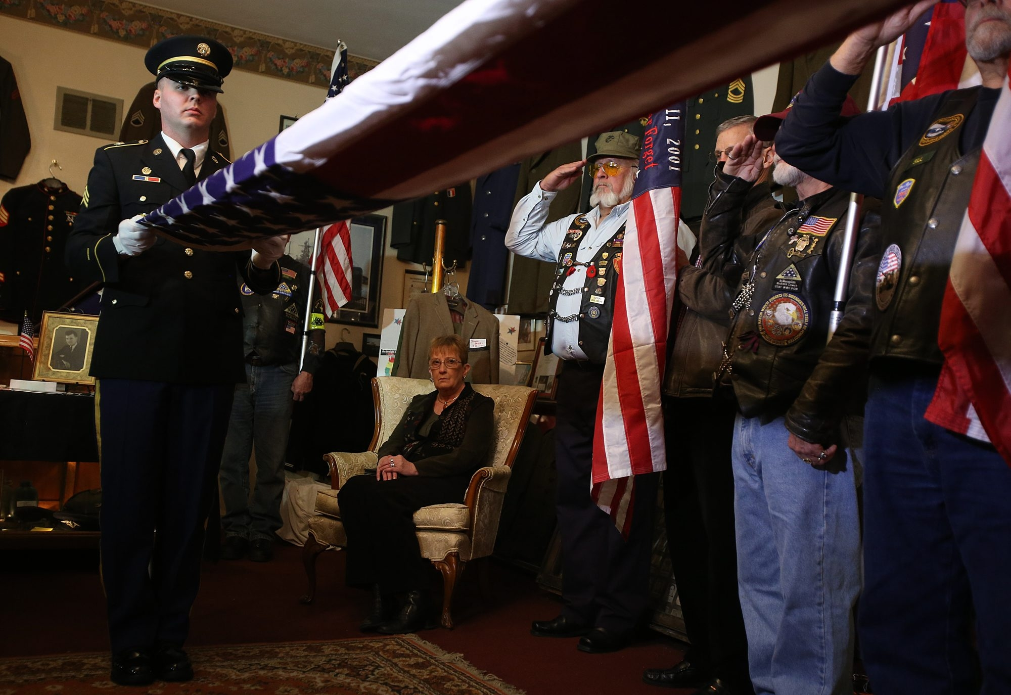 Nancy Cederman, of Akron, niece of Staff Sgt. Kendall Morrow, watches as honor guard folds U.S. flag while Patriot Guard Riders salute in Purple Heart ceremony Monday. Her uncle died  in action in 1943; the medal had been missing but was found in Rochester. Photo gallery at BuffaloNews.com.