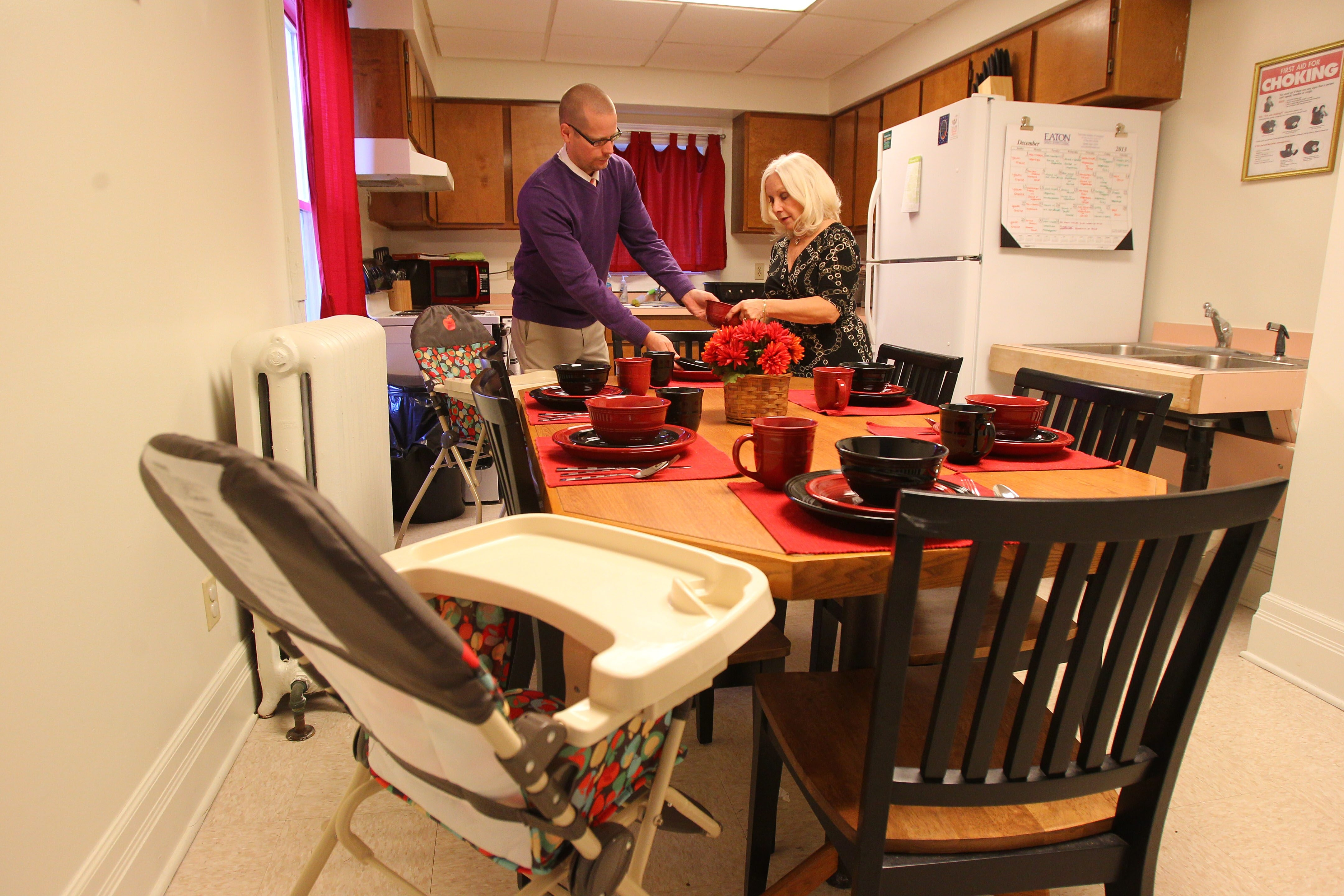 Jeffrey Wierzbicki, director of youth services, and Jennifer Tresch, director of development, set the table in the kitchen of the building for young mothers.