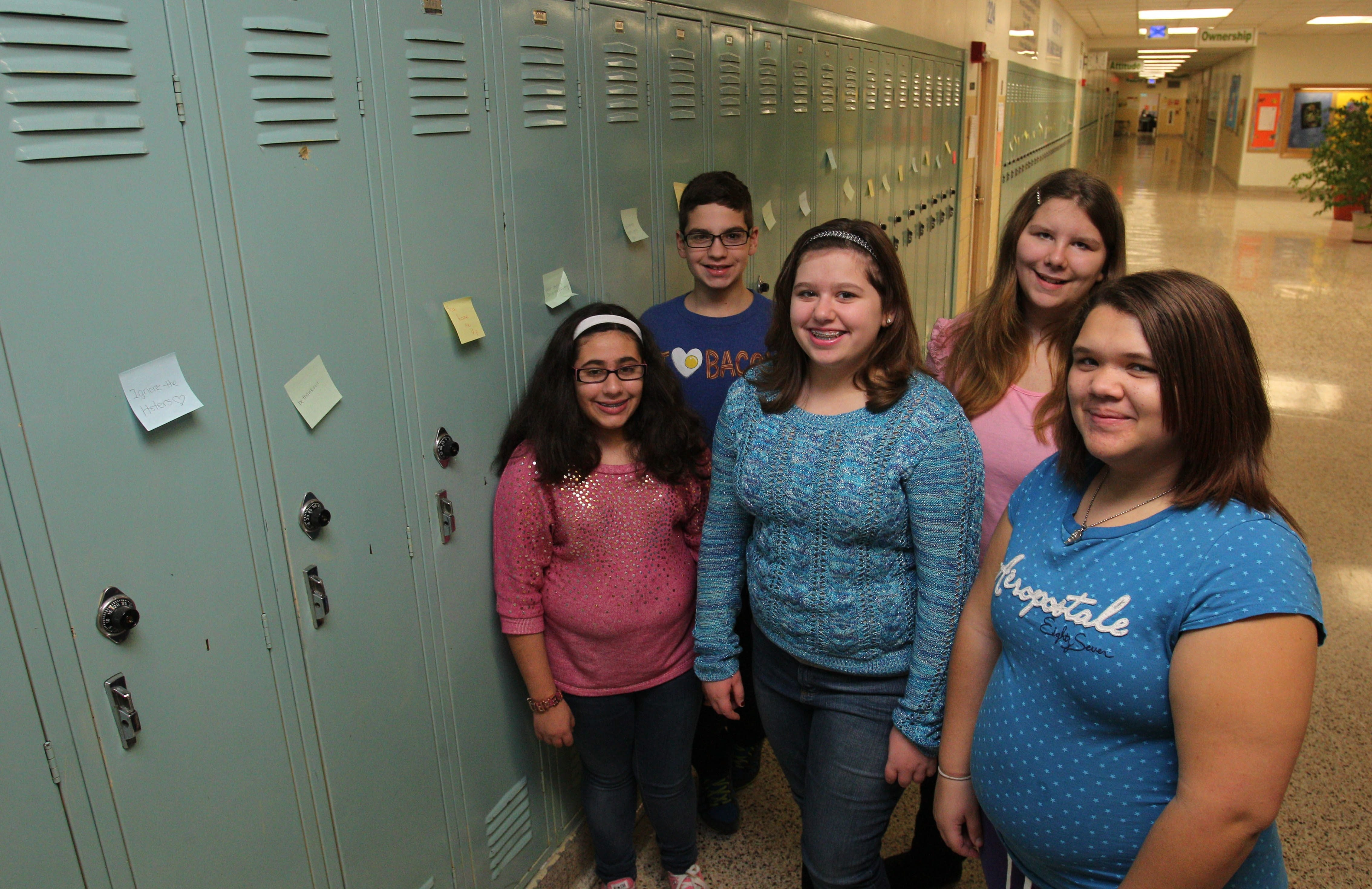 Post-it Project members from left, Chloe Avino, Zach Kalinowski, Alyssa Germano, Victoria Carberry and Ariana Rodeboro pose near lockers adorned with some of their handiwork at Hoover Middle School on Wednesday.