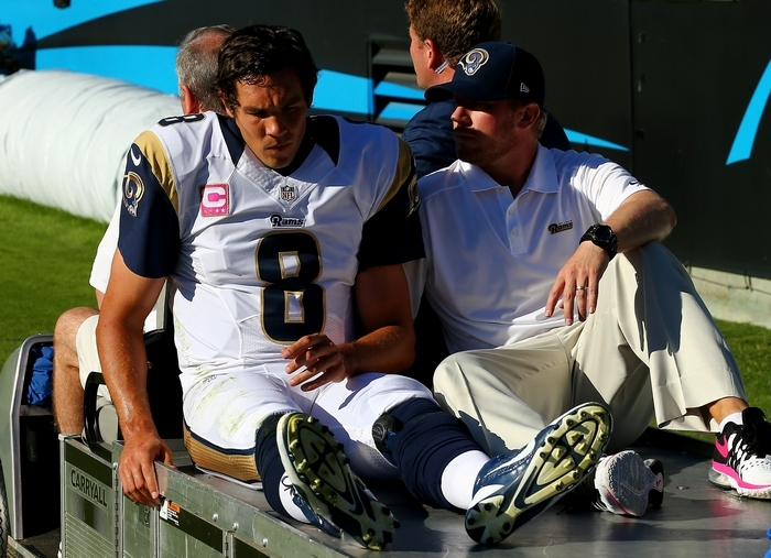 St. Louis Rams quarterback Sam Bradford leaves the field with a leg injury after being knocked out of bounds by Mike Mitchell of the Carolina Panthers. The Rams fear that Bradford suffered a significant knee injury. (Getty Images)