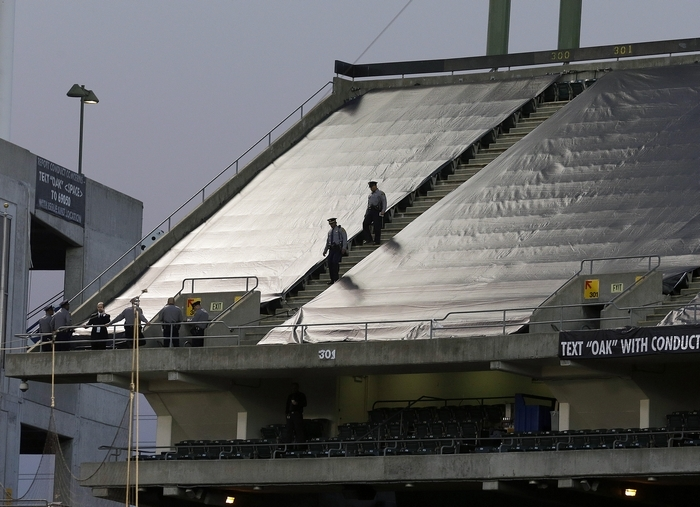 Law enforcement officials walk in the upper deck of O.co Coliseum after Sunday's game between the Oakland Raiders and the Tennessee Titans in Oakland, Calif. Authorities say a football fan jumped after the game from the third deck of the stadium, injuring herself and a man one level below who tried to catch her. (Associated Press)