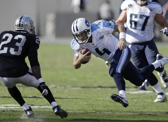 Titans quarterback Ryan Fitzpatrick runs for yardage against Oakland's Tracy Porter during Tennessee's victory over the Raiders on Sunday. (Associated Press)