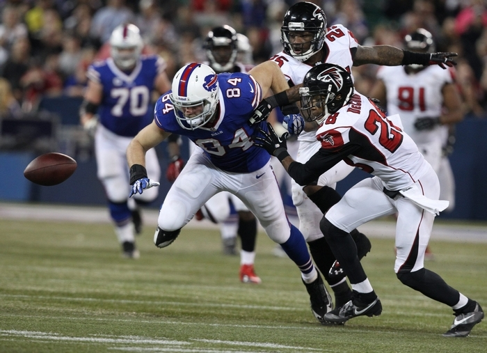 Falcons safety William Moore (25) knocks the ball loose from Bills tight end Scott Chandler in overtime on Sunday. (James P. McCoy/Buffalo News)