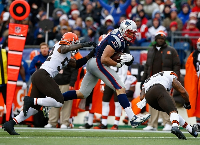Rob Gronkowski of the Patriots is about to take a hit on the knee last Sunday from Browns safety T.J. Ward, right, knocking  him out of the New England lineup for the rest of the season. (Getty Images)