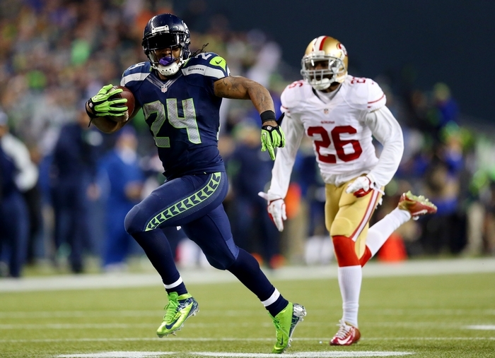 Running back Marshawn Lynch No. 24 of the Seattle Seahawks scores a 40-yard touchdown against cornerback Tramaine Brock #26 of the San Francisco 49ers in the third quarter during the 2014 NFC Championship at CenturyLink Field Sunday in Seattle. (Getty Images)