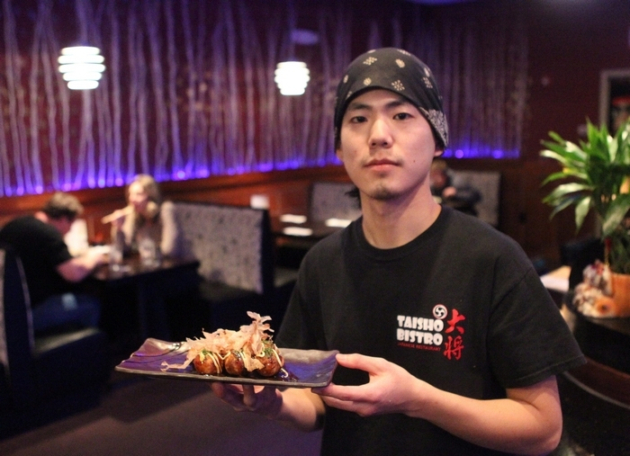 Andy Huang, a co-owner and chef of Taisho Bistro, with plate of octopus fritters. (John Hickey/Buffalo News)