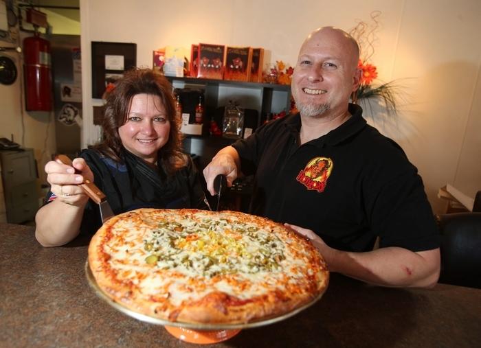 Diane Notto-Hamric and Eric Hamric show the Ring of Fire pizza at Hotroxs on Southwestern Boulevard in Hamburg. (Robert Kirkham/Buffalo News)