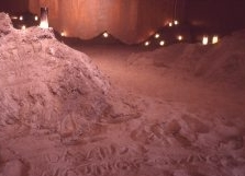 For an installation in Hallwalls, Karen Finley painted an entire room gold and filled it with several tons of sand and dozens of candles. Visitors were invited to wade into the room's artificial dunes and write the names of friends and family members they had lost to AIDS into the soft sand.