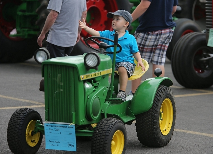 Bradley Milligan, 3, of Cheektowaga, looks ready to drive  Wednesday as he sits on a tractor on the first day of the Erie County Fair in Hamburg. (Charles Lewis/Buffalo News)