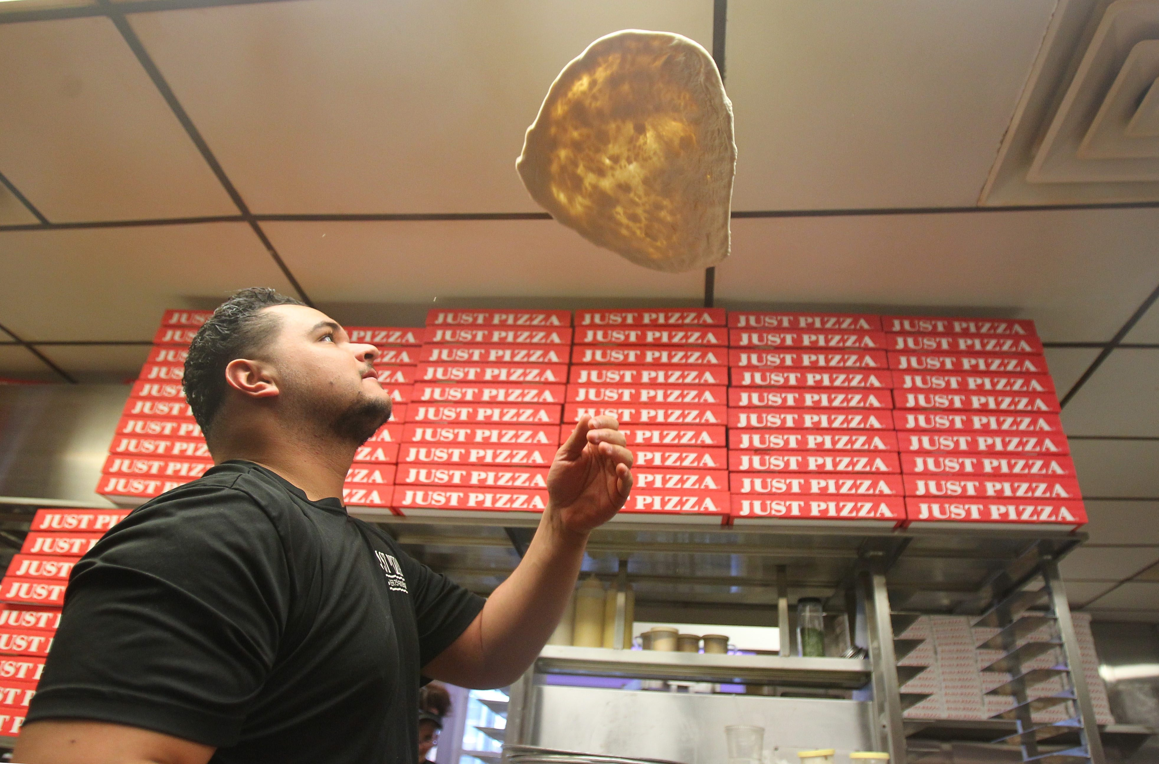 Rudy Alloy III throws some dough for a New York style pizza Friday at Just Pizza on Elmwood Avenue. Come Sunday, the restaurant expects to go through 50 gallons of pizza sauce and 1,800 pounds of mozzarella cheese.
