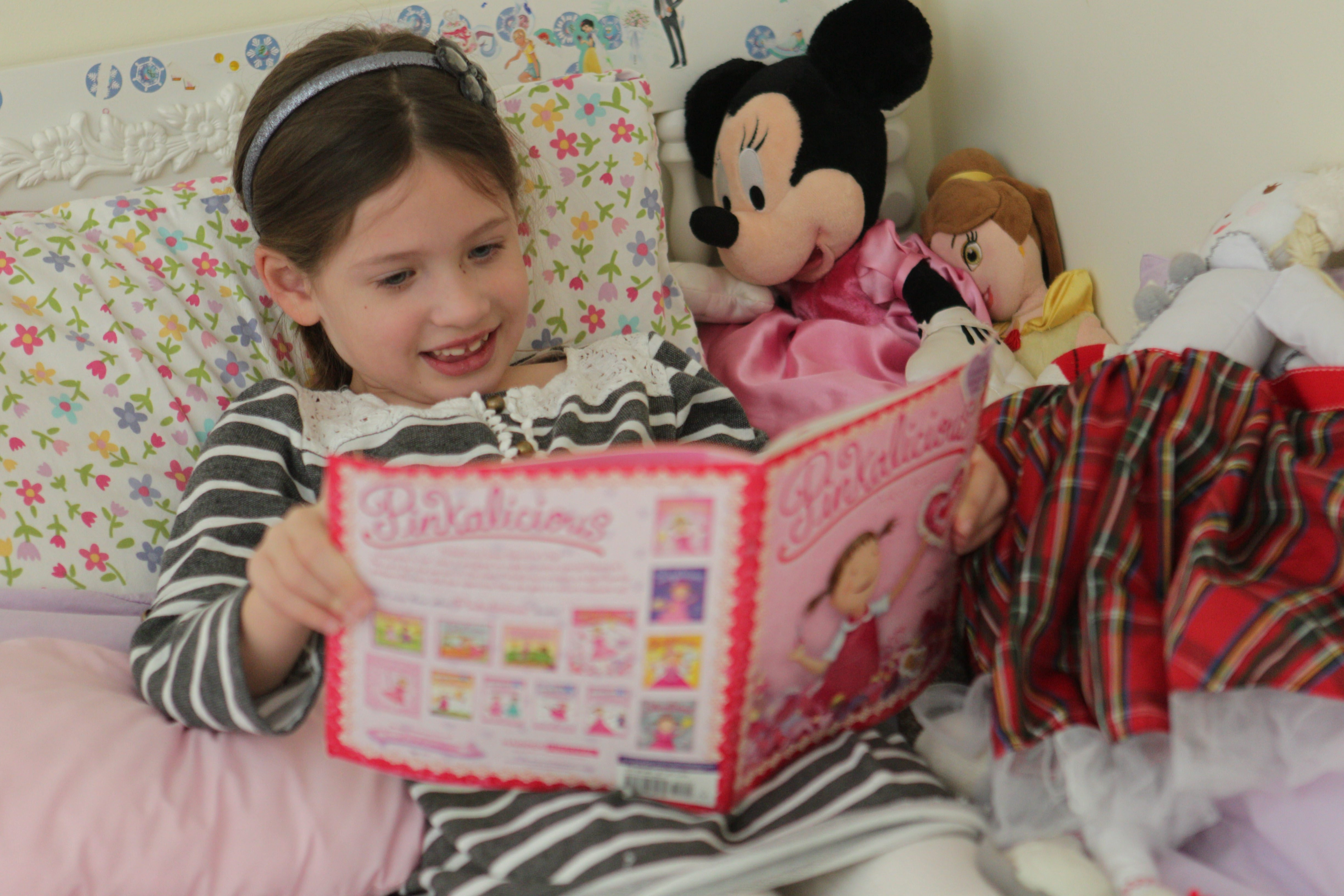 "Sophia Capuana, 6, reads a ""Pinkalicious"" book in her bedroom."