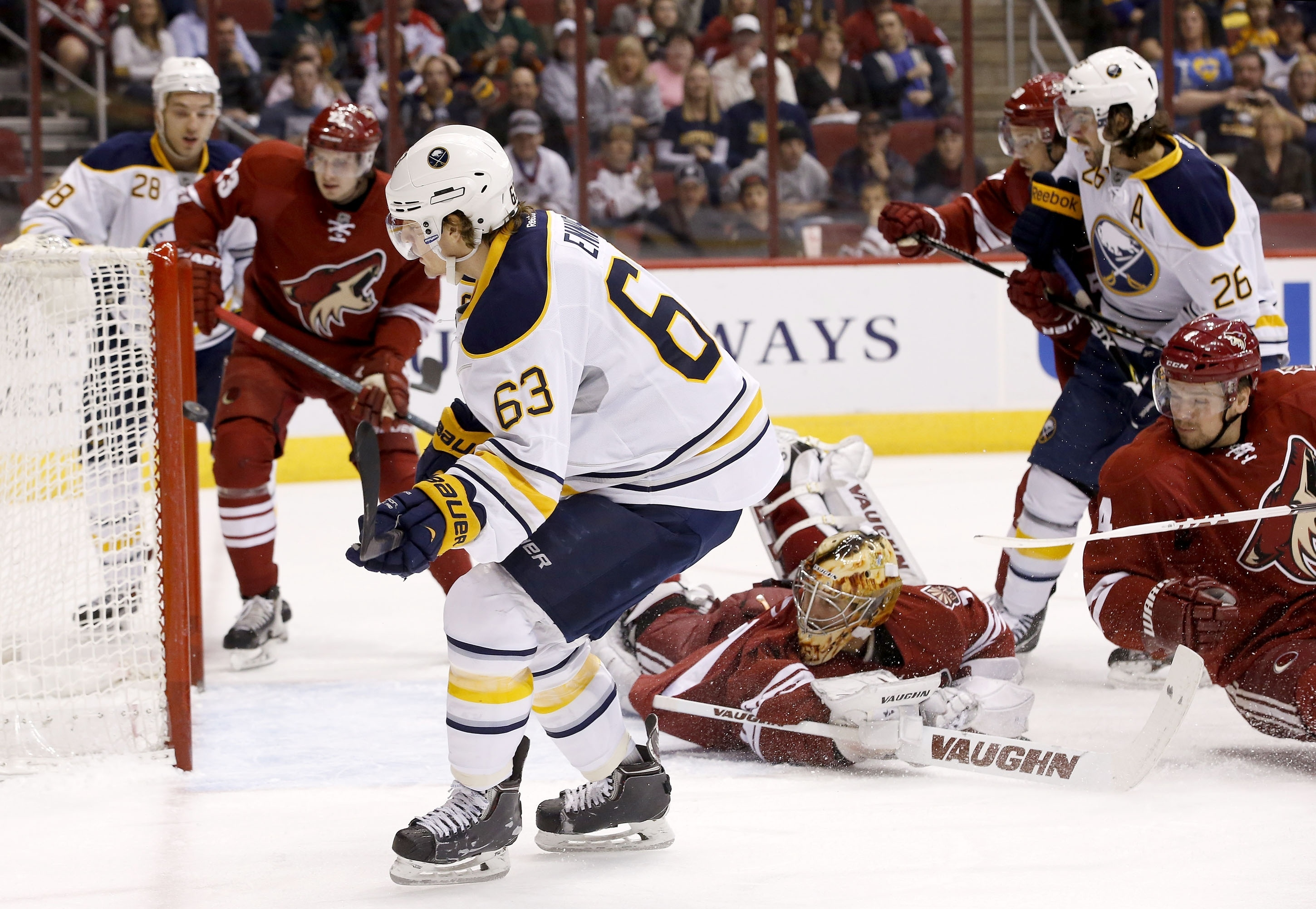 Buffalo's Tyler Ennis gets the puck past a diving Thomas Greiss, the Coyotes' goaltender, to score the Sabres' first goal.