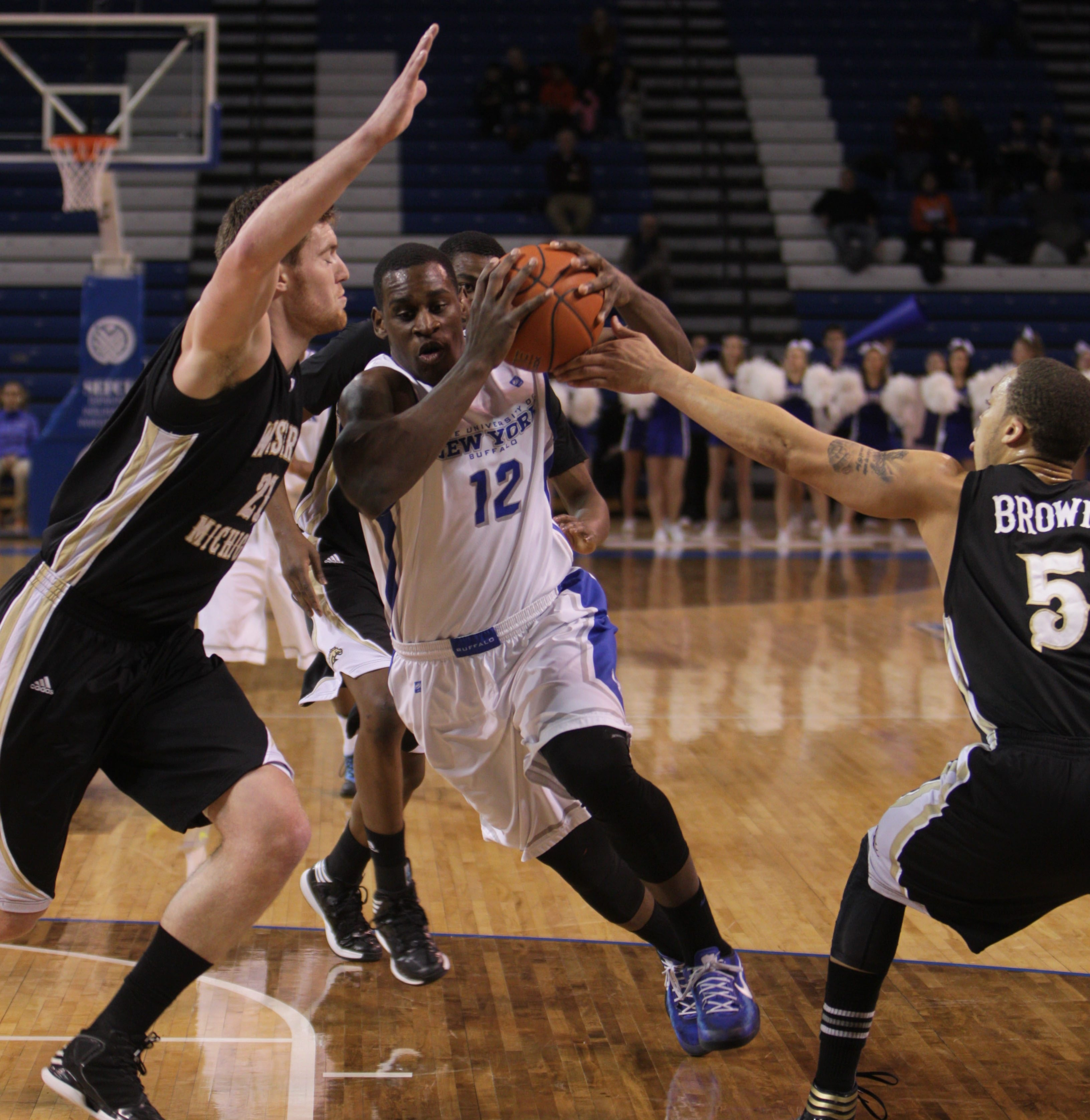 UB's Javon McCrea drives past Western Michigan's Shayne Whittington, left, and David Brown for two points. McCrea scored a game-high 20 points.