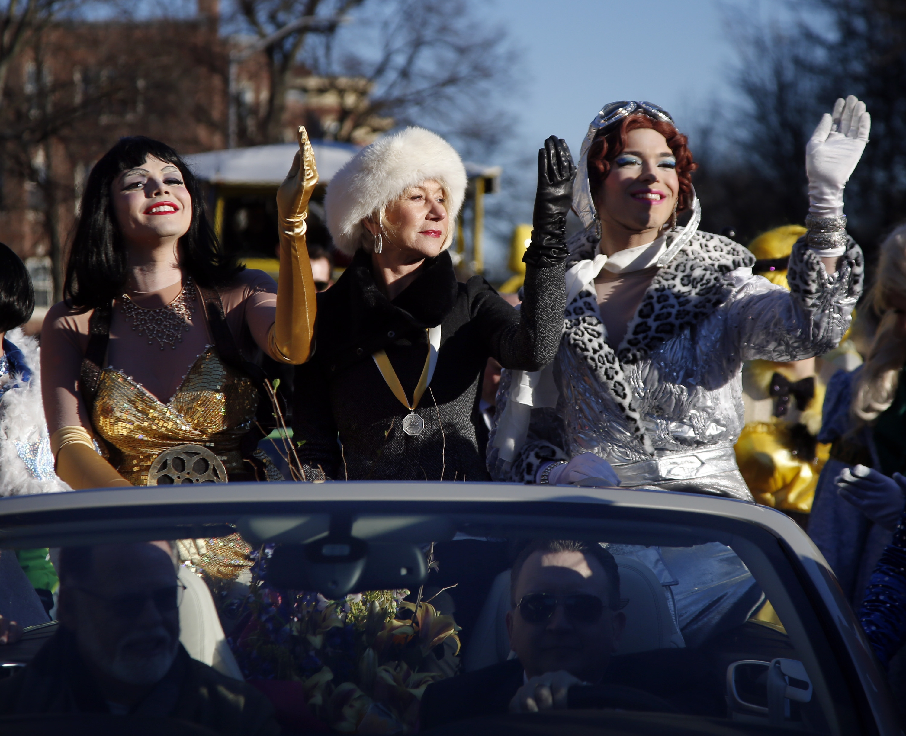 Actress Helen Mirren, in the hat, practices her royal wave while parading through Harvard Square with  drag actor Tony Oblen in Cambridge, Mass., Thursday.