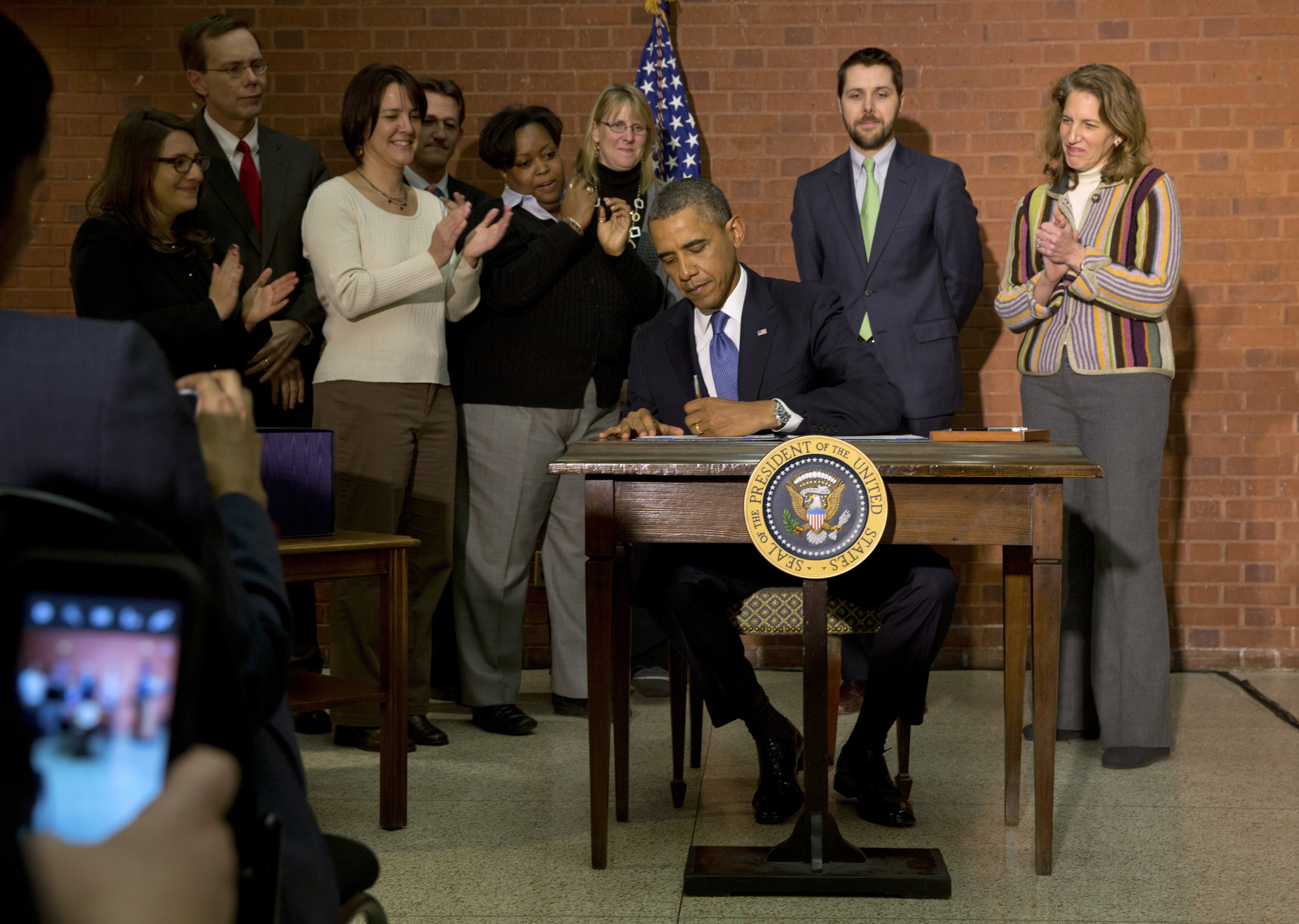 President Obama signs the spending bill that reduces some of the effects of the sequester. (New York Times photo)