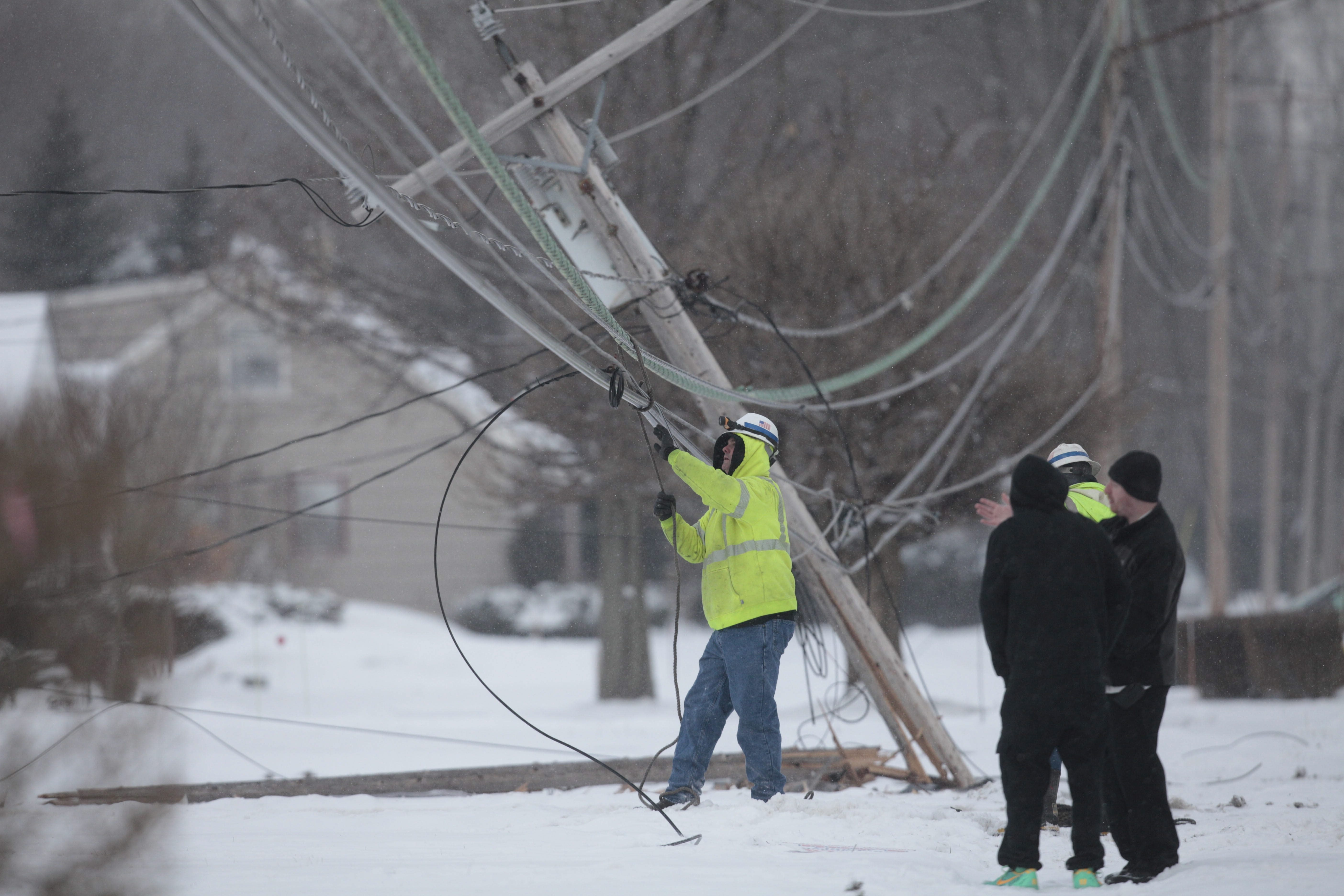 Police and utility workers respond to North French Road in Amherst after a car took out a utility pole and ended up crashing into a house causing a natural gas leak, Friday, Jan. 24, 2014.  (Derek Gee/Buffalo News)