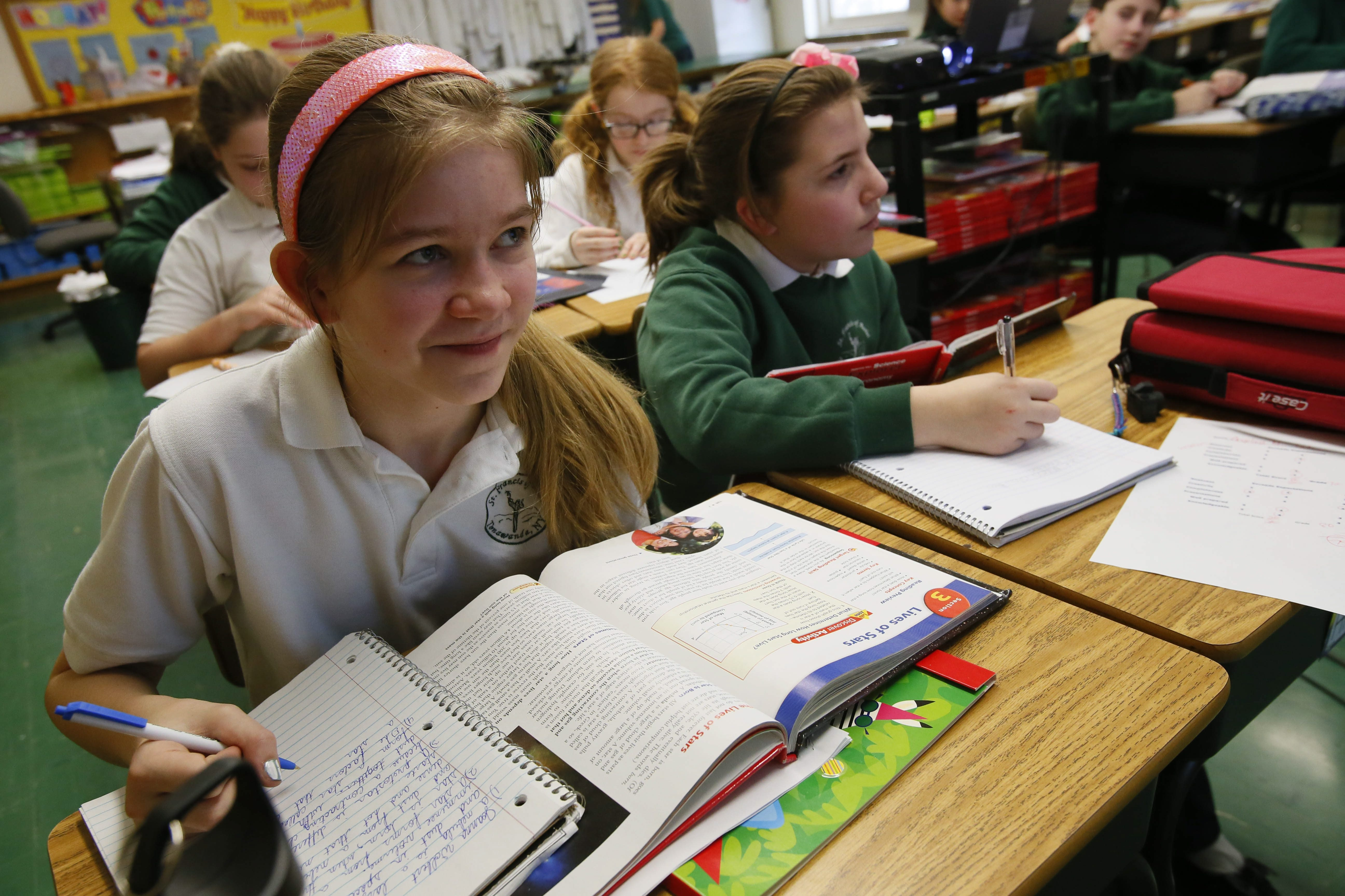 Sixth-grade students Joanna Wolbert, left, and Angelina Meranto hit the books during science class Thursday at St. Francis of Assisi School in the City of Tonawanda.