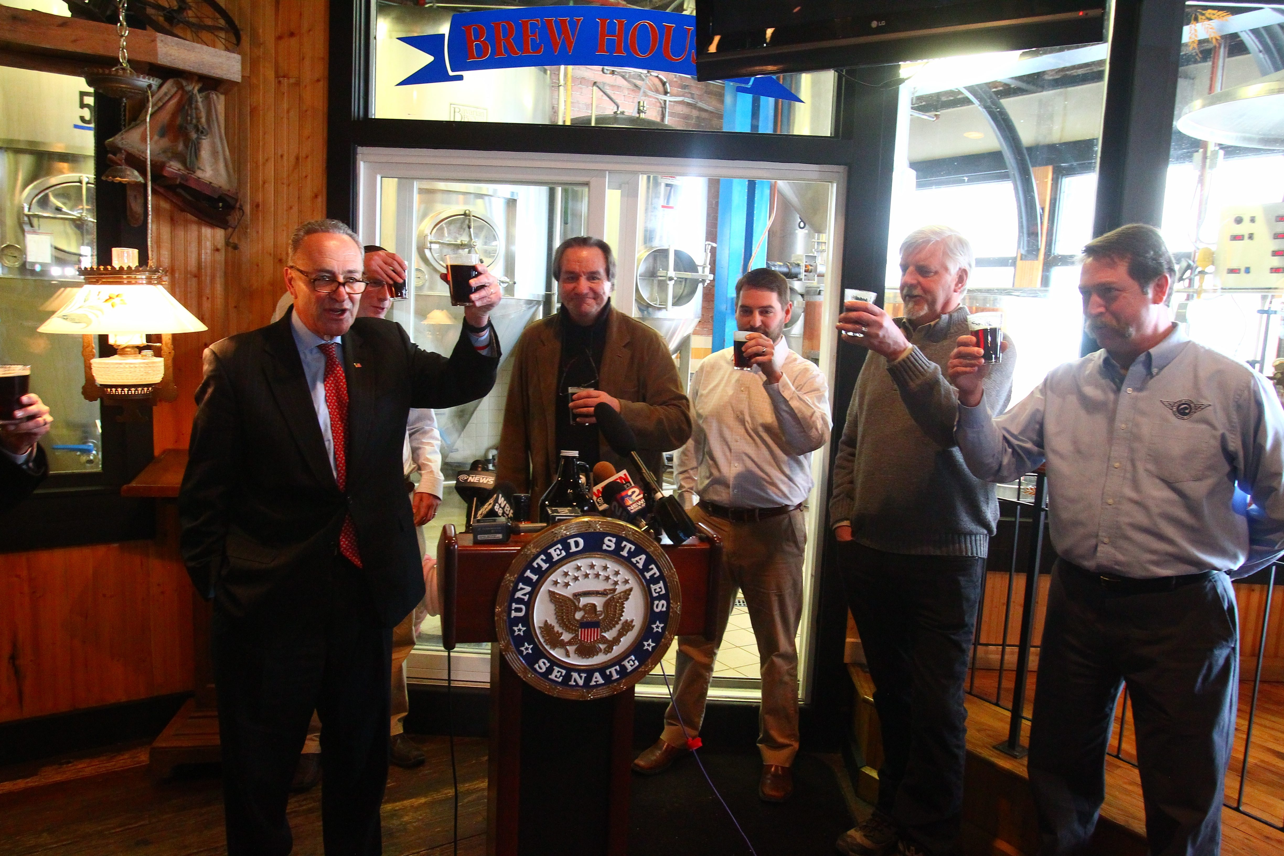 Sen. Charles Schumer offers a toast from lectern at news conference in Pearl Street Grill & Brewery as, from right, Tim Herzog, Doug Swift, Jeff Ware, Earl Ketry and Matt Kahn back his Small BREW Act.