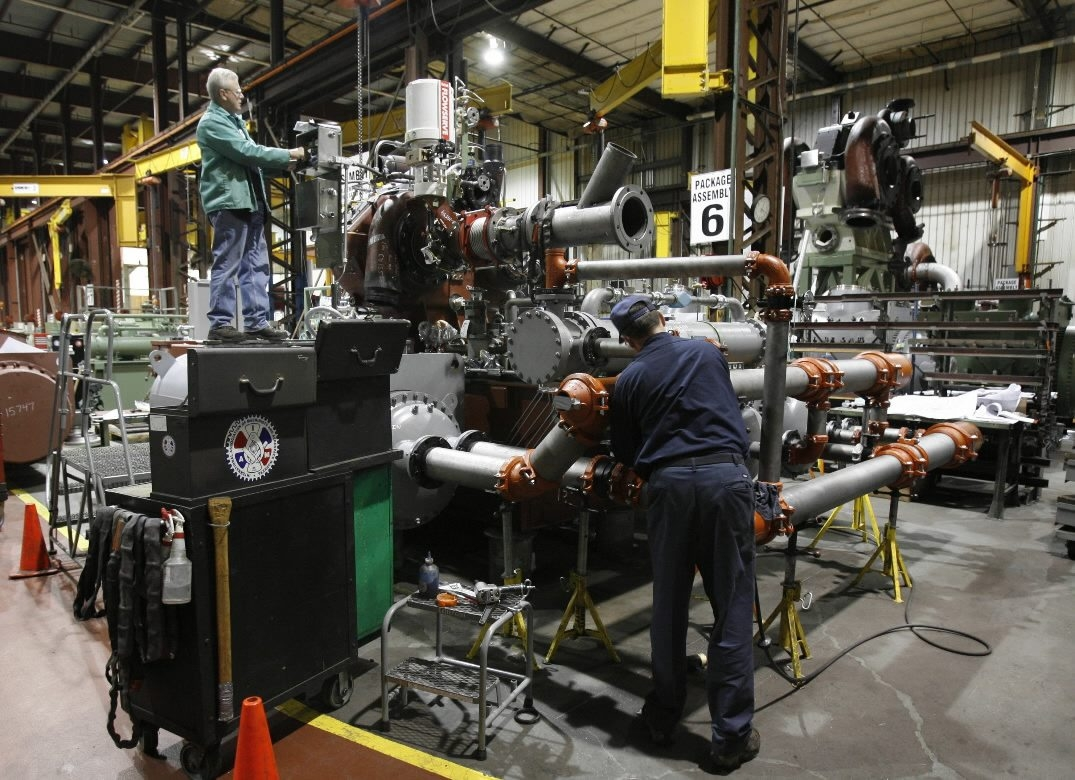 Cameron International workers assemble a giant compressor system at the Cheektowaga plant.