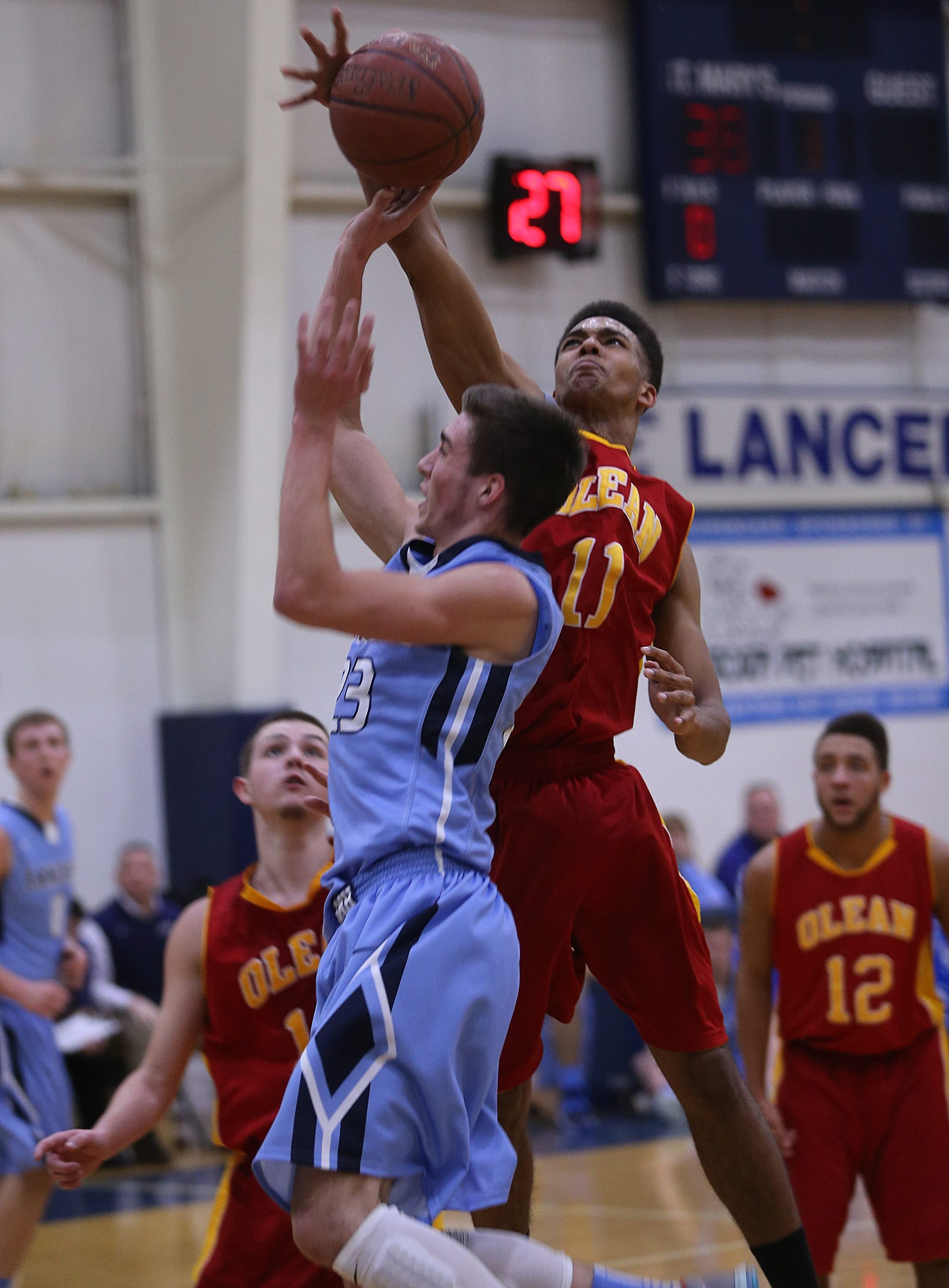Tyler English (23) of St. Mary's gets his shot knocked away by Olean's Wil Bathurst during Tuesday's game in Lancaster.