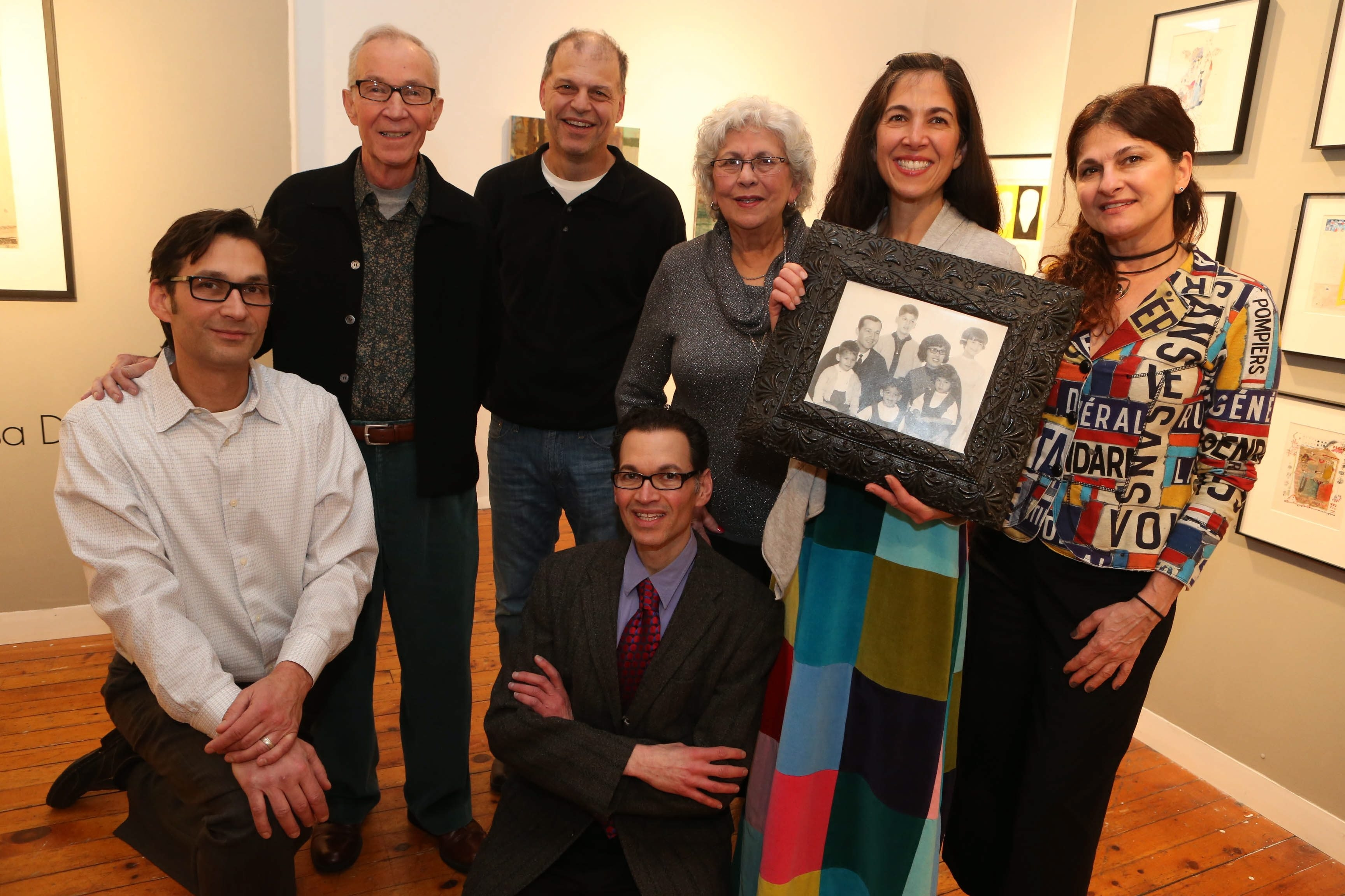 "The DiBernardos replicate a vintage family photo at the Carnegie Art Center in North Tonawanda on Sunday. From left, standing, Vena, Guy, Camille, Vanessa and Luanne; kneeling, Jon and Van. The family was there for the opening of the exhibit ""Relative Lines"" and for Vena's 80th birthday."