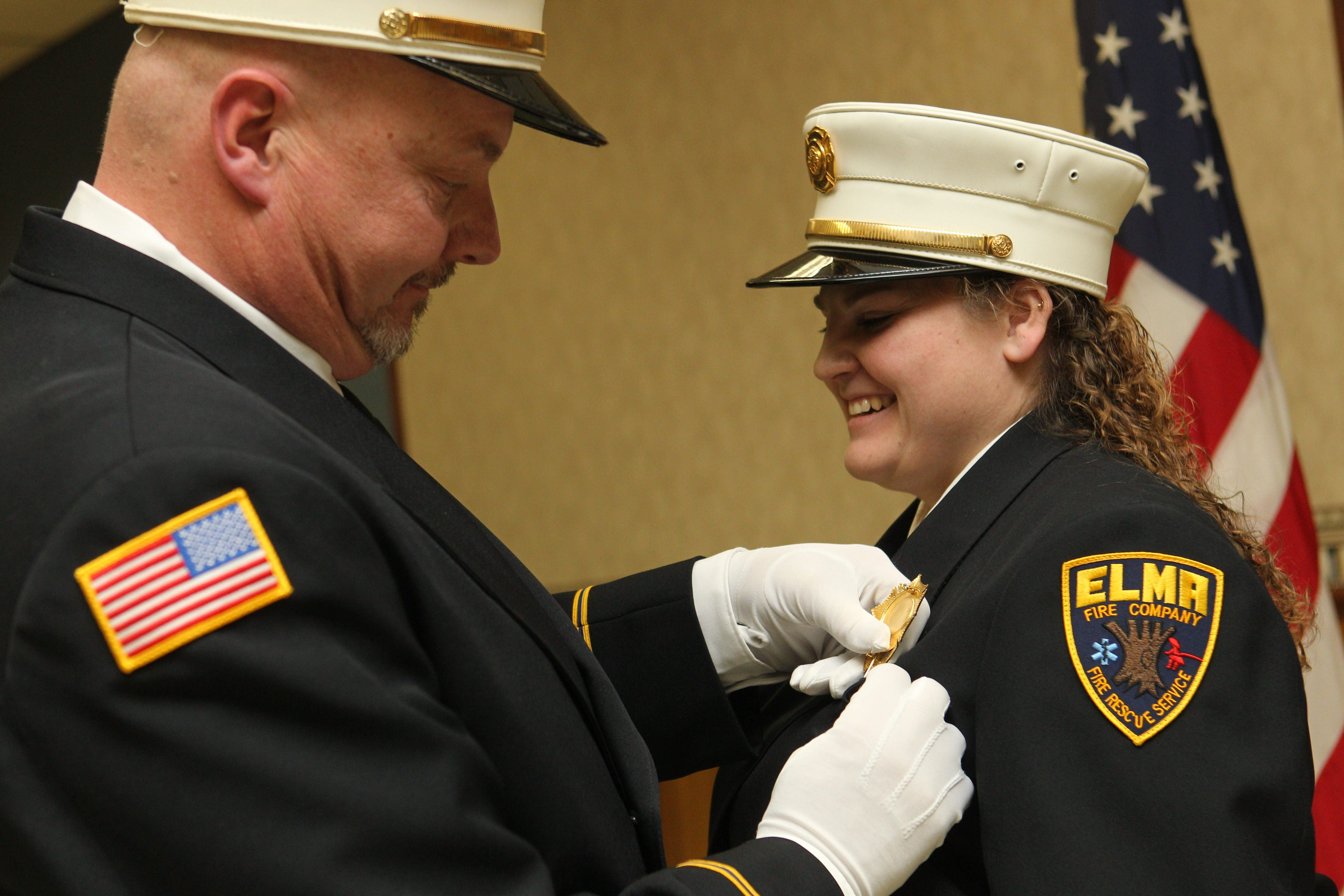 Outgoing Chief Mike Kalczynski pins a badge on Betsy Goinski after she took the oath of office Saturday to become the first woman chief of the Elma Volunteer Fire Company.