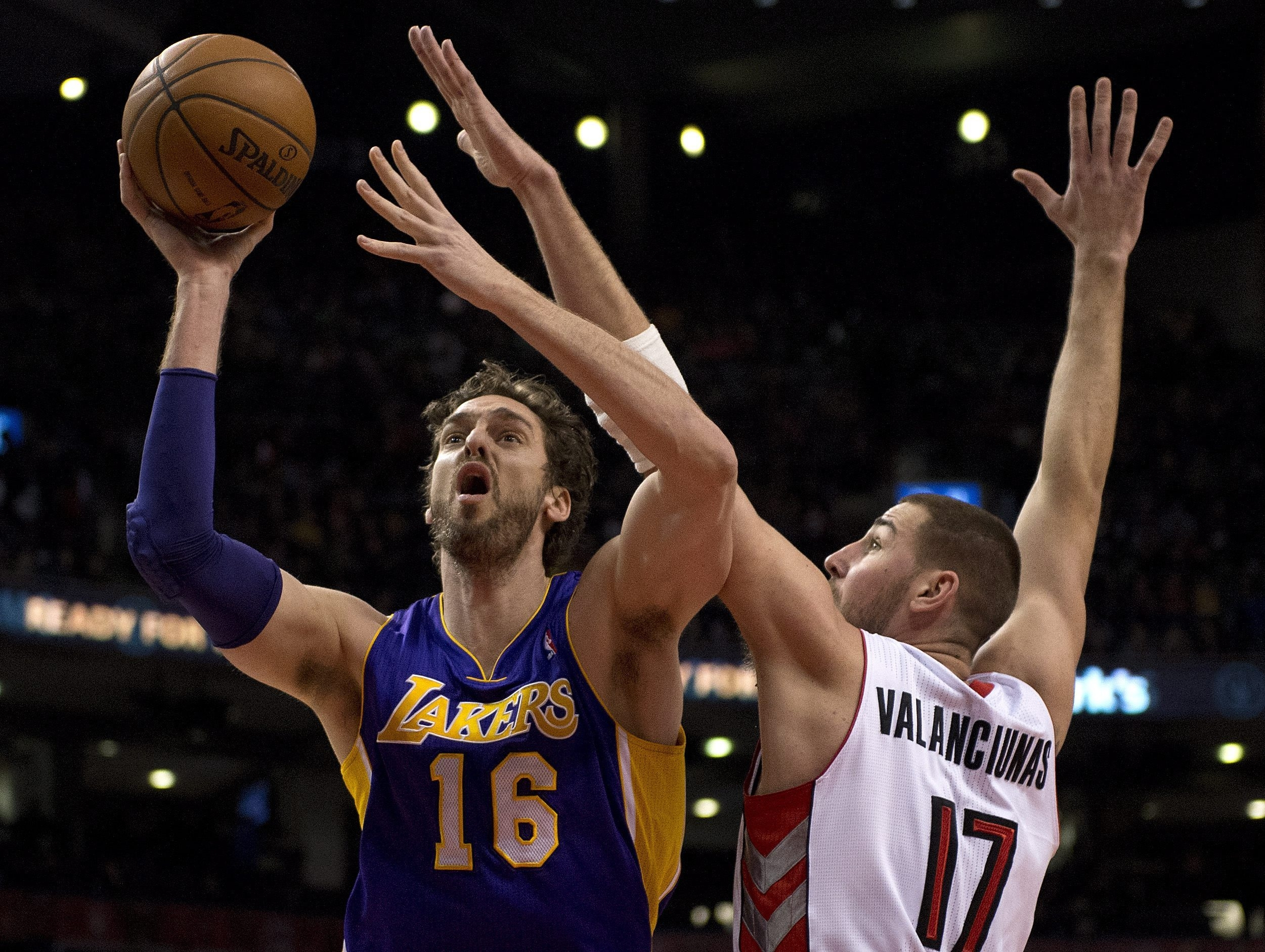 Lakers center Pau Gasol drives to the hoop past Toronto Raptors center Jonas Valanciunas during the first half in Air Canada Centre on Sunday.   Associated Press