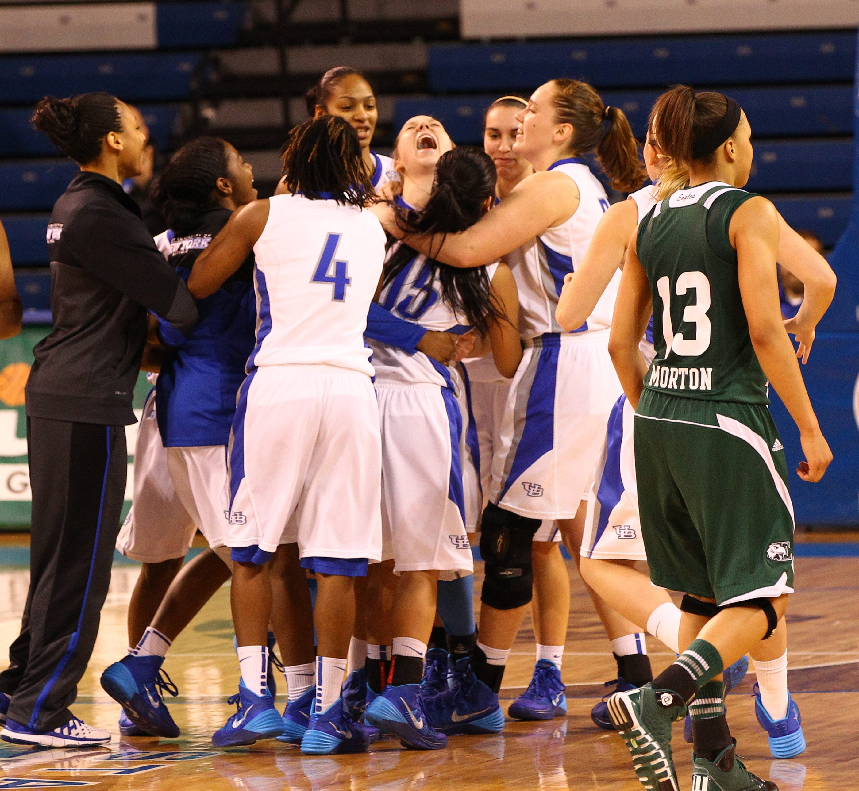 UB's Mackenzie Loesing, center, is mobbed by her teammates after scoring the game winning basket in overtime against Eastern Michigan Saturday at Alumni Arena.