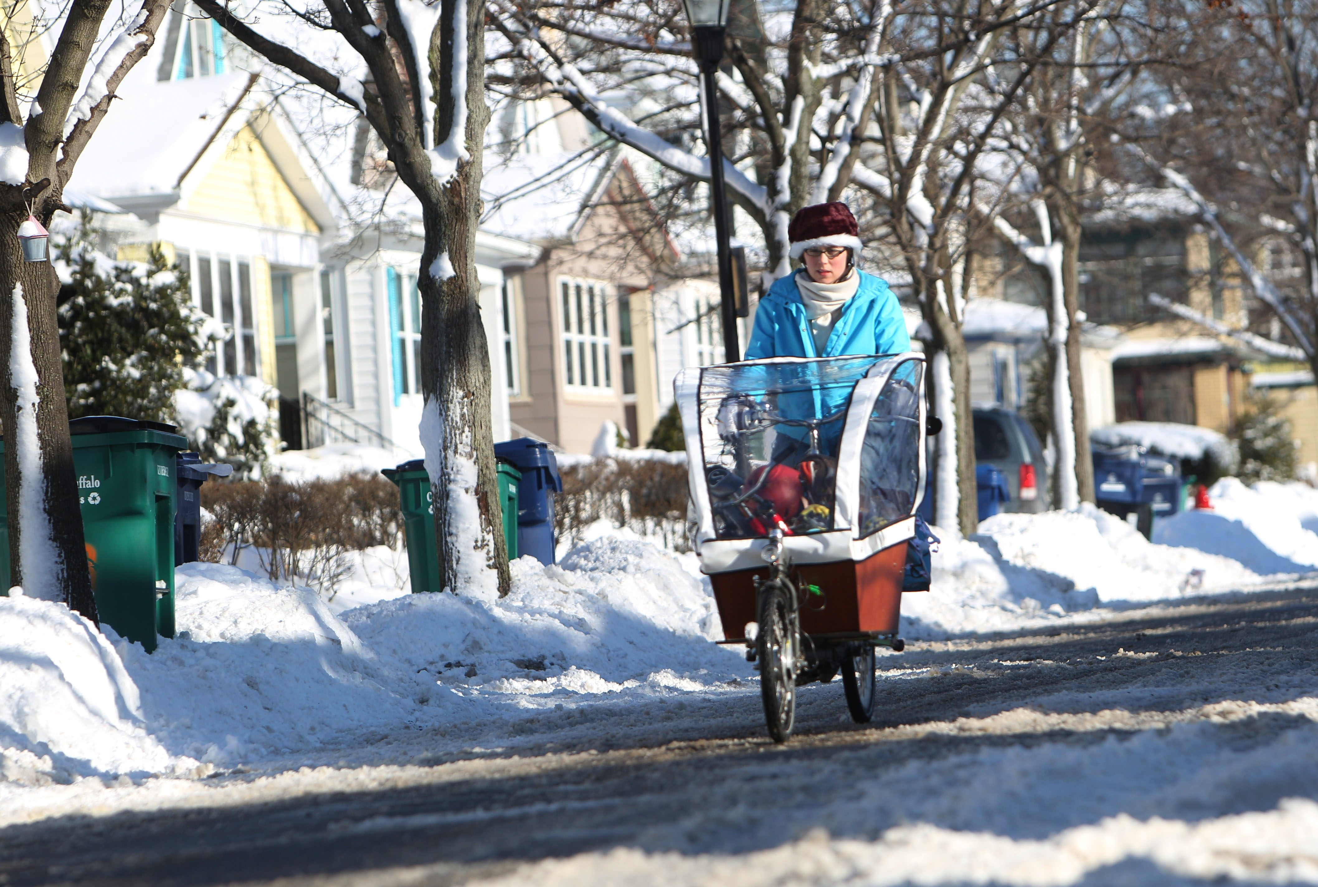 Stacy Bisker rides home from the zoo with her son Oliver Patterson, 4, Thursday, Jan. 9, 2014.  The family doesn't own a car and this is their first winter in Buffalo, so Stacy, her husband and four children are learning how to navigate the snowy streets with a bike.  Her bike is a cargo bike with a canopy to protect from the wind rain and snow. She arrives on her street.