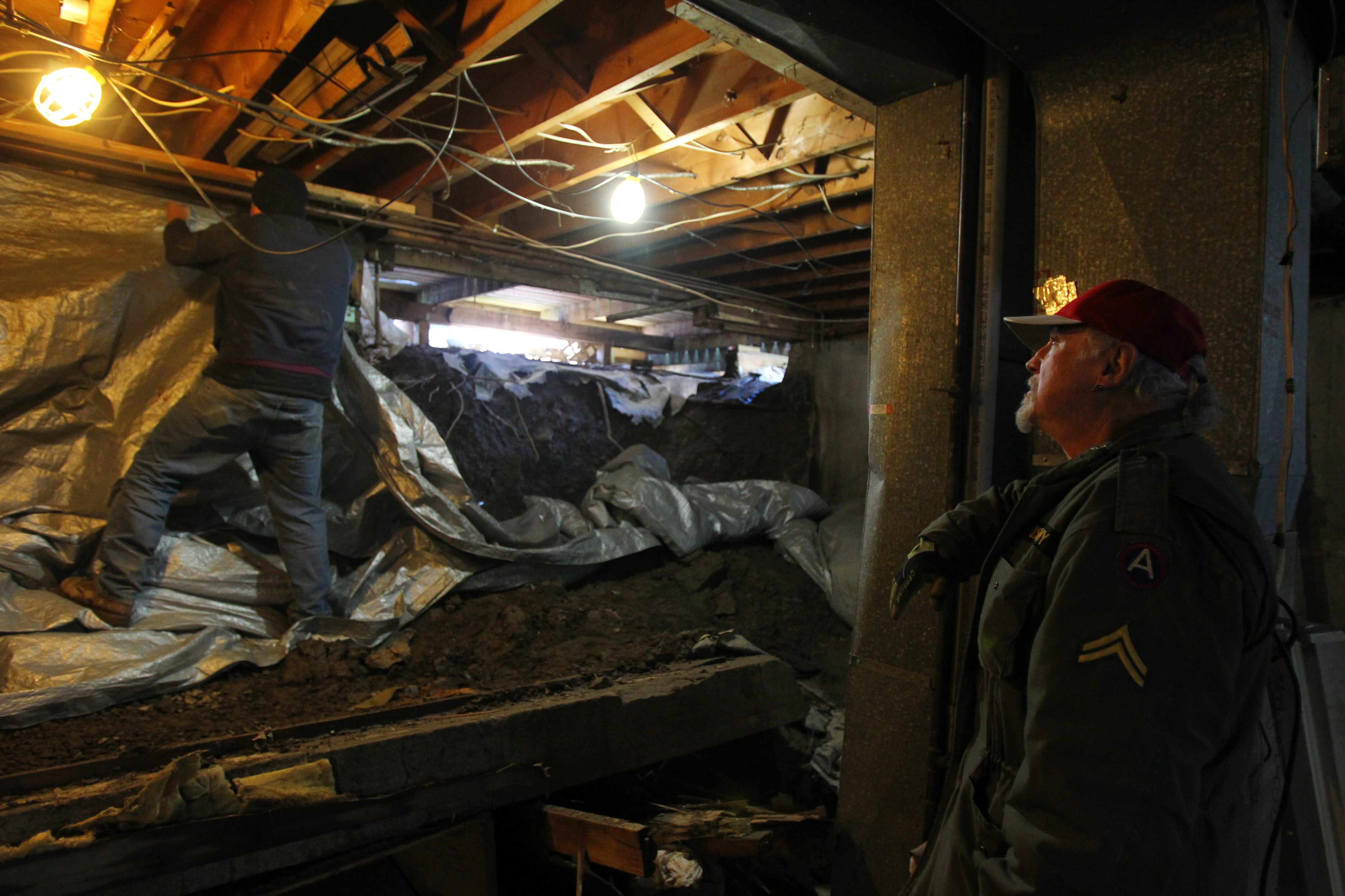Jonny Robbins watches as contractor Bruce Edwards secures a tarp in his basement Friday.  Last weekend, his sump pump burned out, and floodwaters destroyed a part of the foundation of his Gregory Drive home in West Seneca.