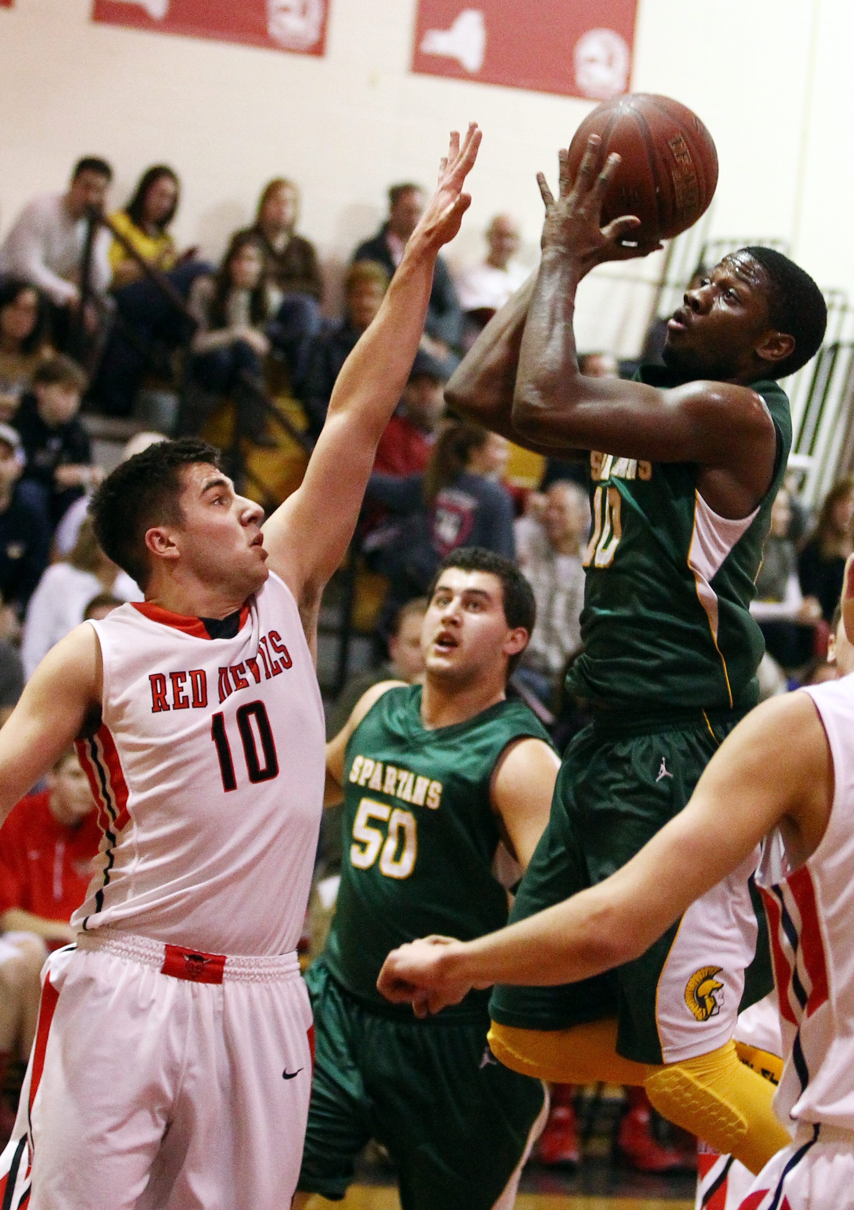 Williamsville North's Sterling Taplin scores two points over Clarence's Elliot Case in the first half.