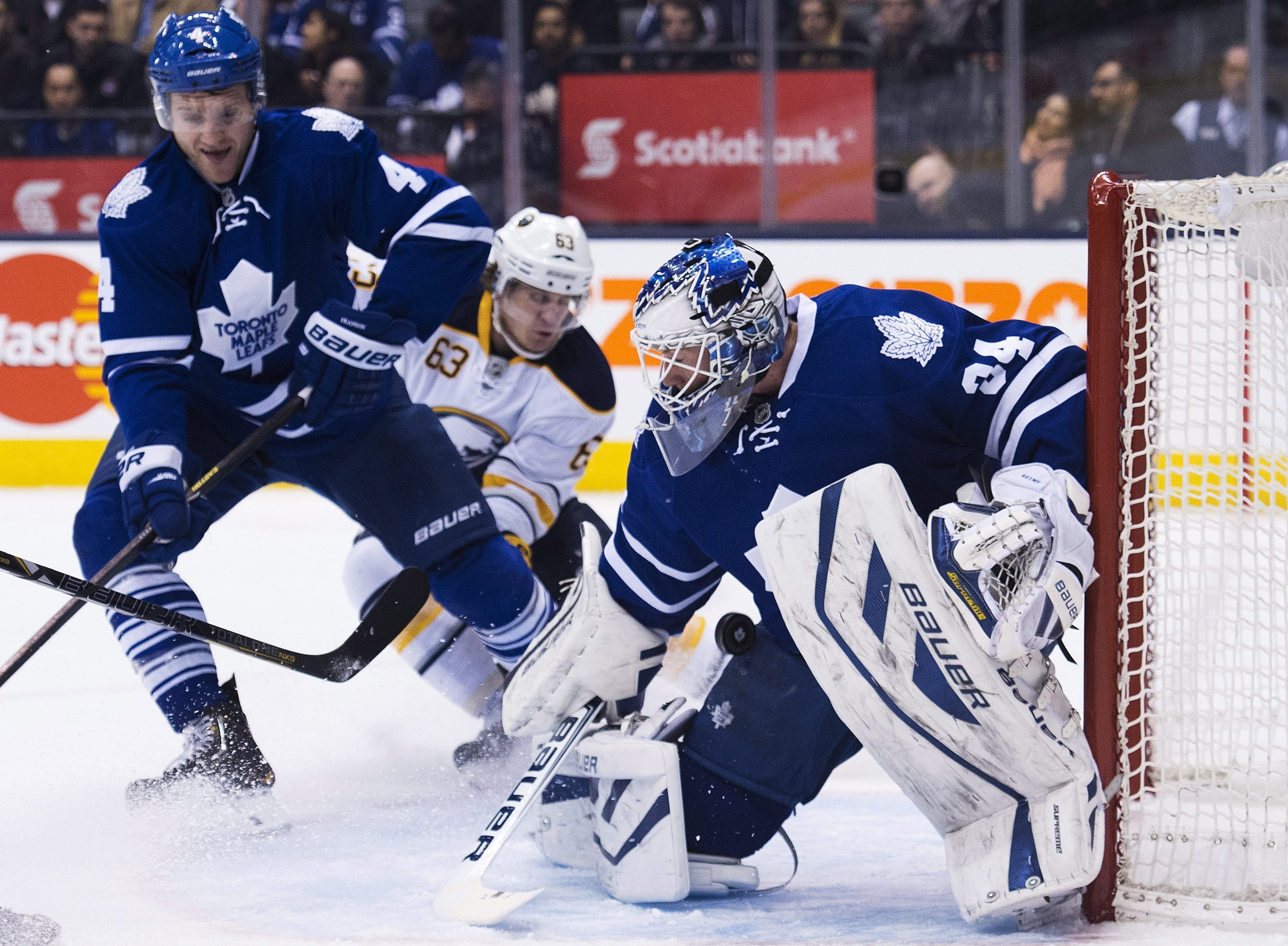 Maple Leafs goalie James Reimer makes a save as Leafs defenseman Cody Franson, left, covers Buffalo's Tyler Ennis.