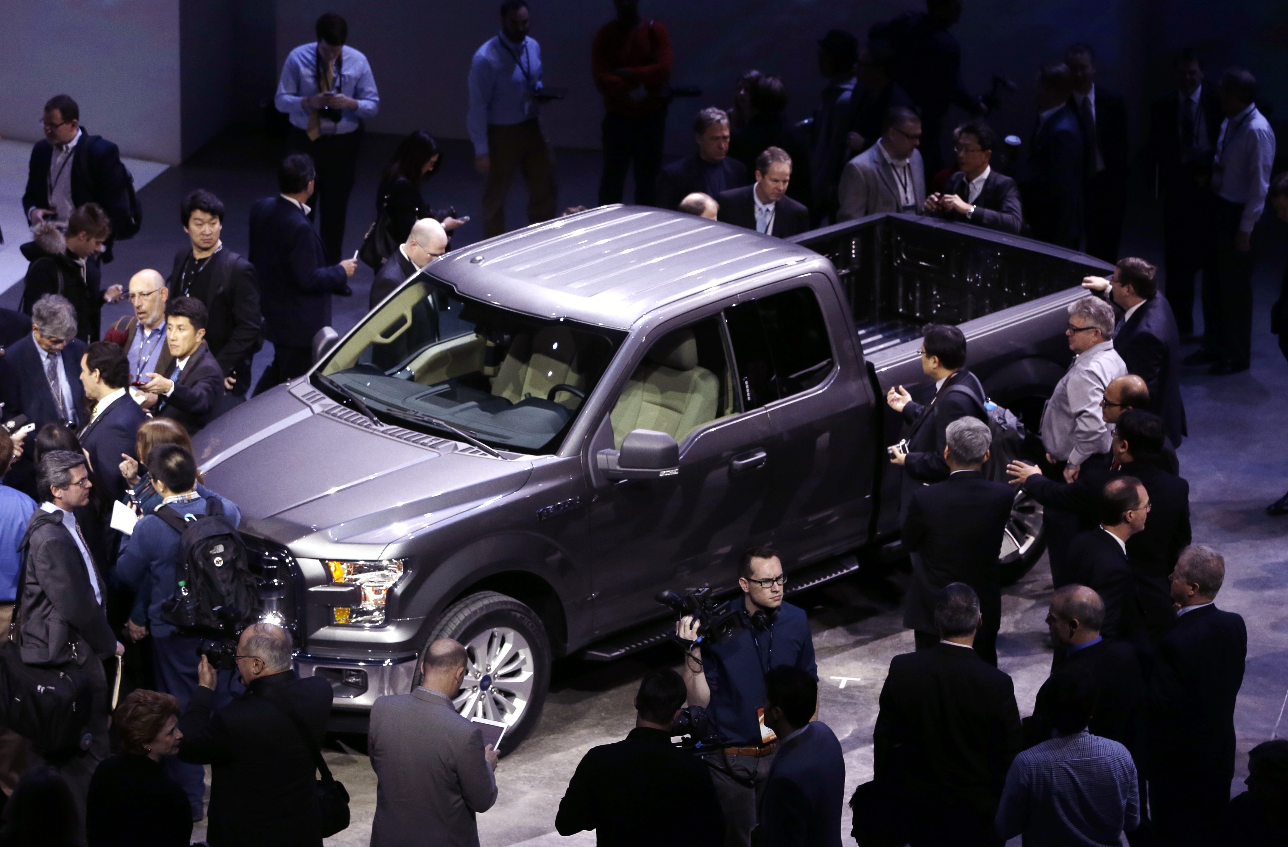Journalists surround the new Ford F-150, the body of which is built almost entirely out of aluminum, at the North American International Auto Show in Detroit on Monday.