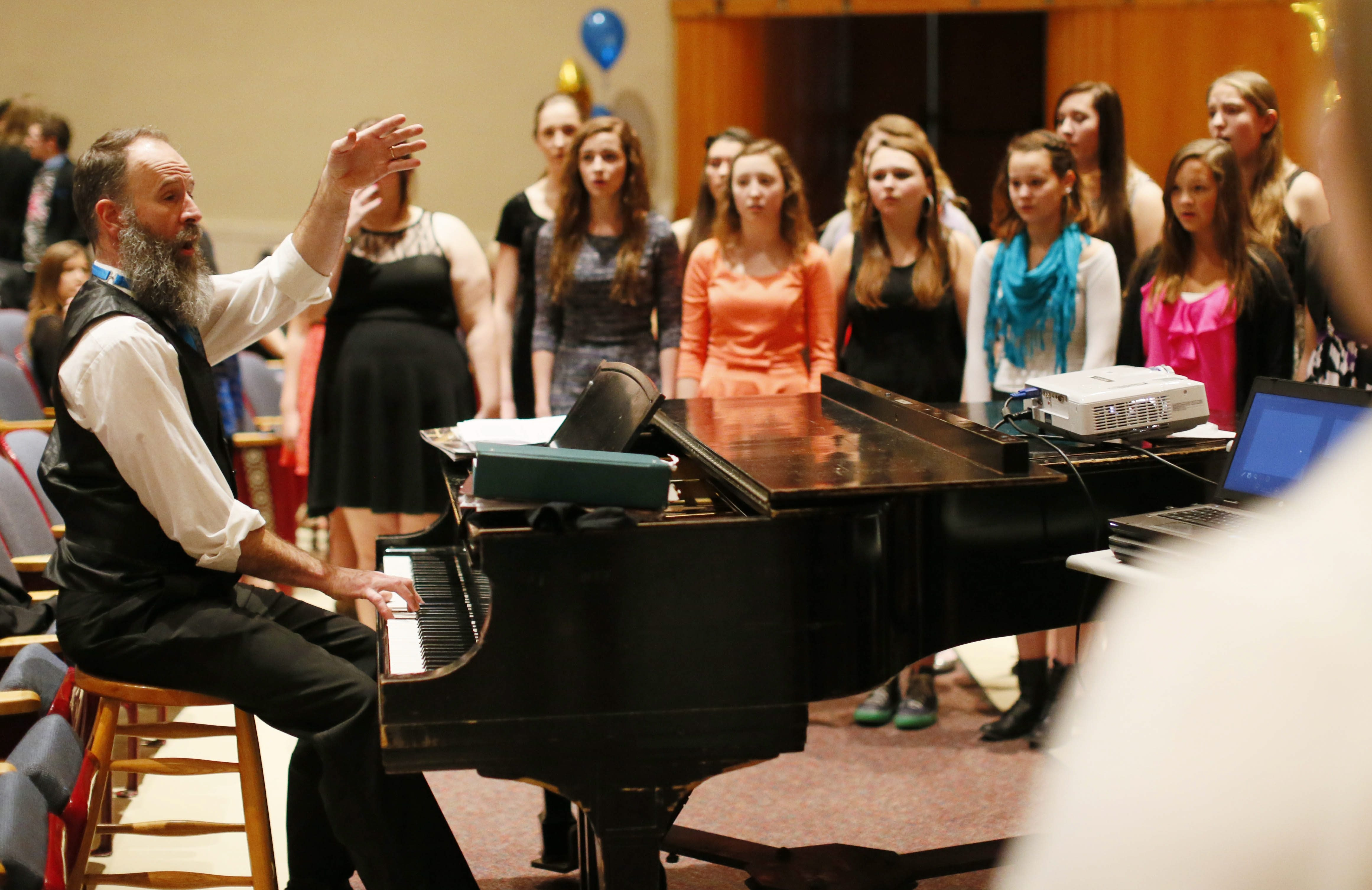 Kent Knappenberger, a Grammy finalist, warms up the Choir of Wolverines before an event Wednesday to honor his achievement.