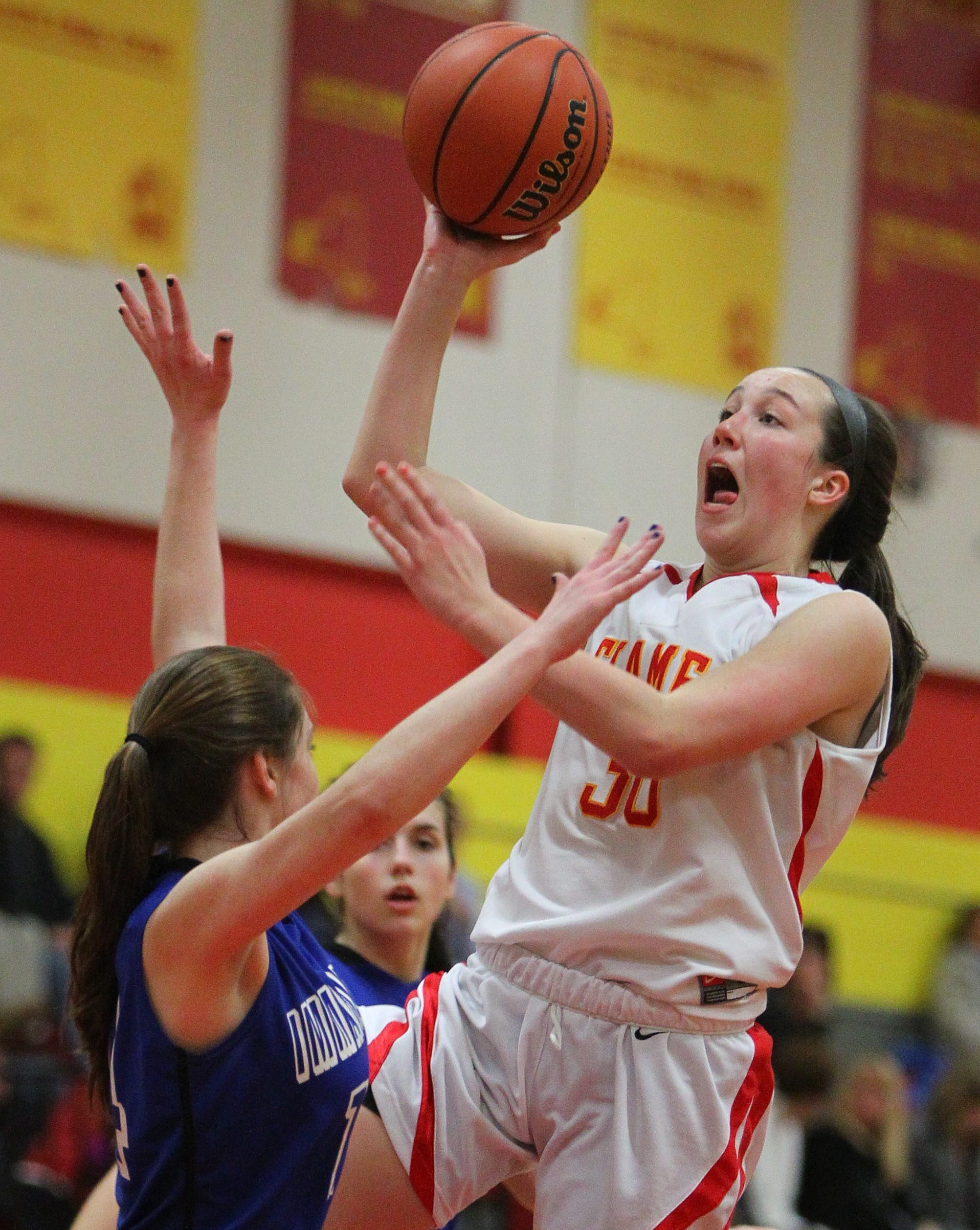 Kenzie Laughlin of Williamsville East drives to the basket against Immaculata's Grace Coughlin in the their game Tuesday night won by the Flames, 40-25.