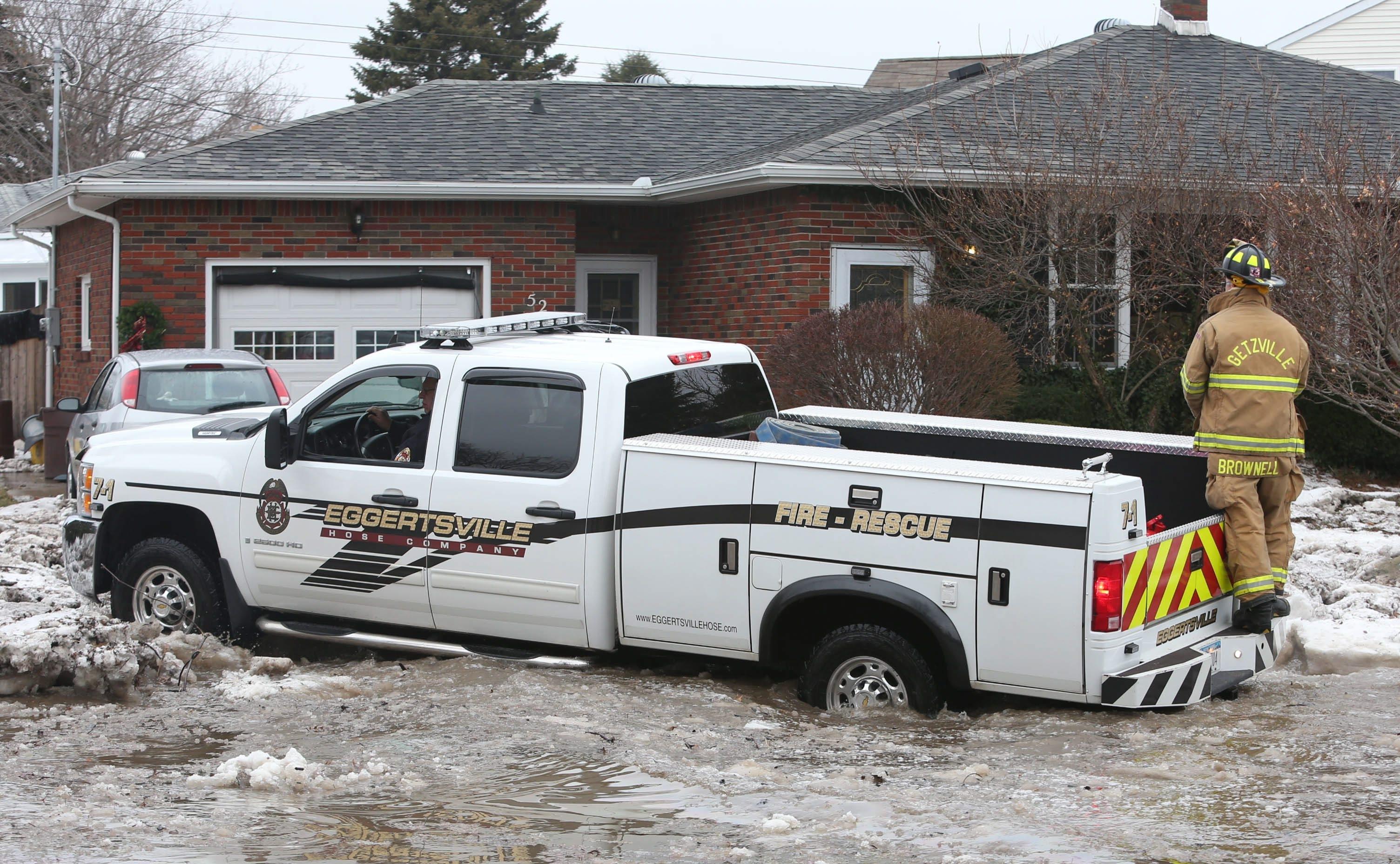 Getzville and Eggertsville volunteer firefighters go door to door offering assistance to residents on Brian Lane in West Seneca on Sunday.