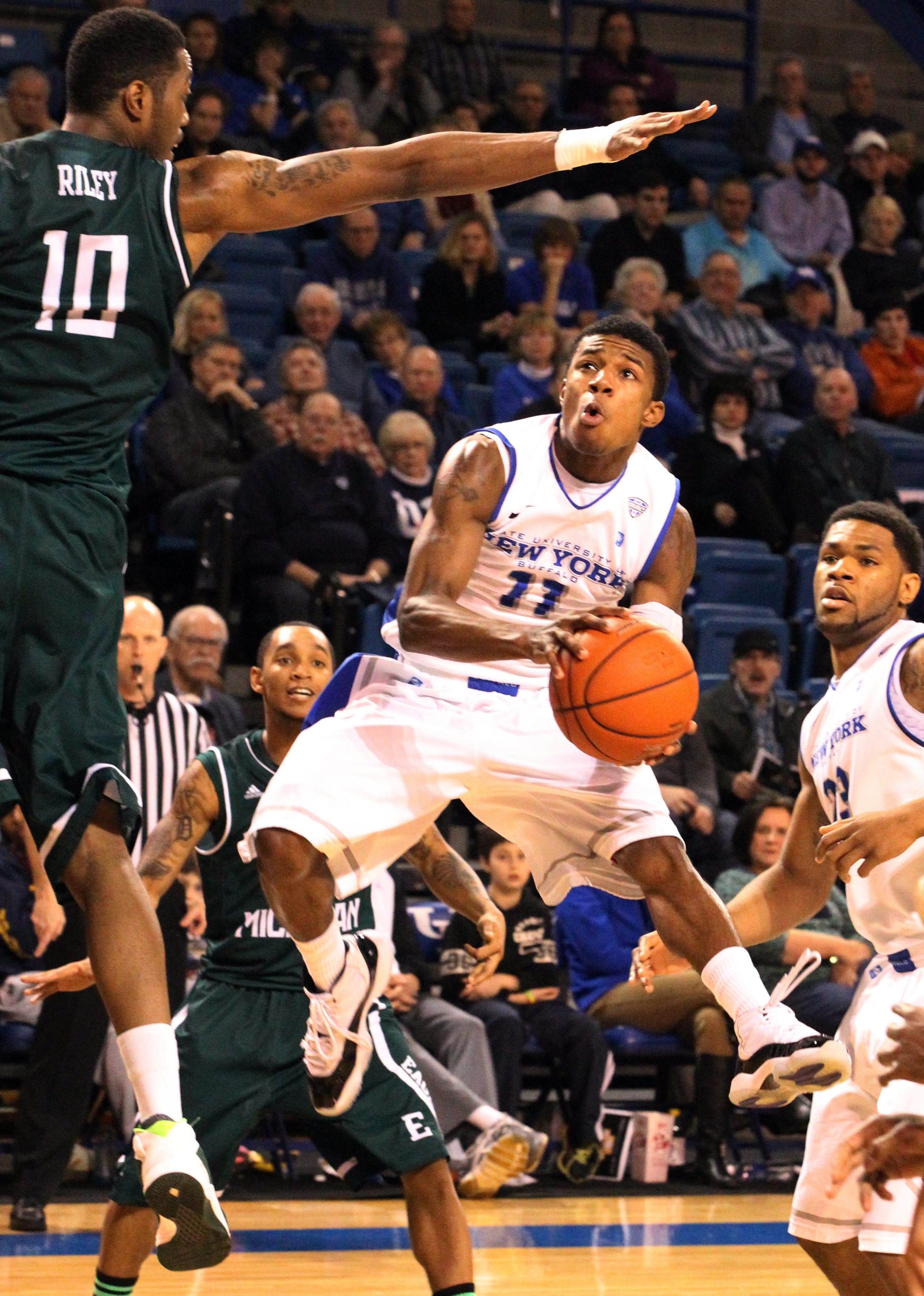 UB guard Shannon Evans (11) scores two points over Eastern Michigan's Da'Shonte Riley (10).