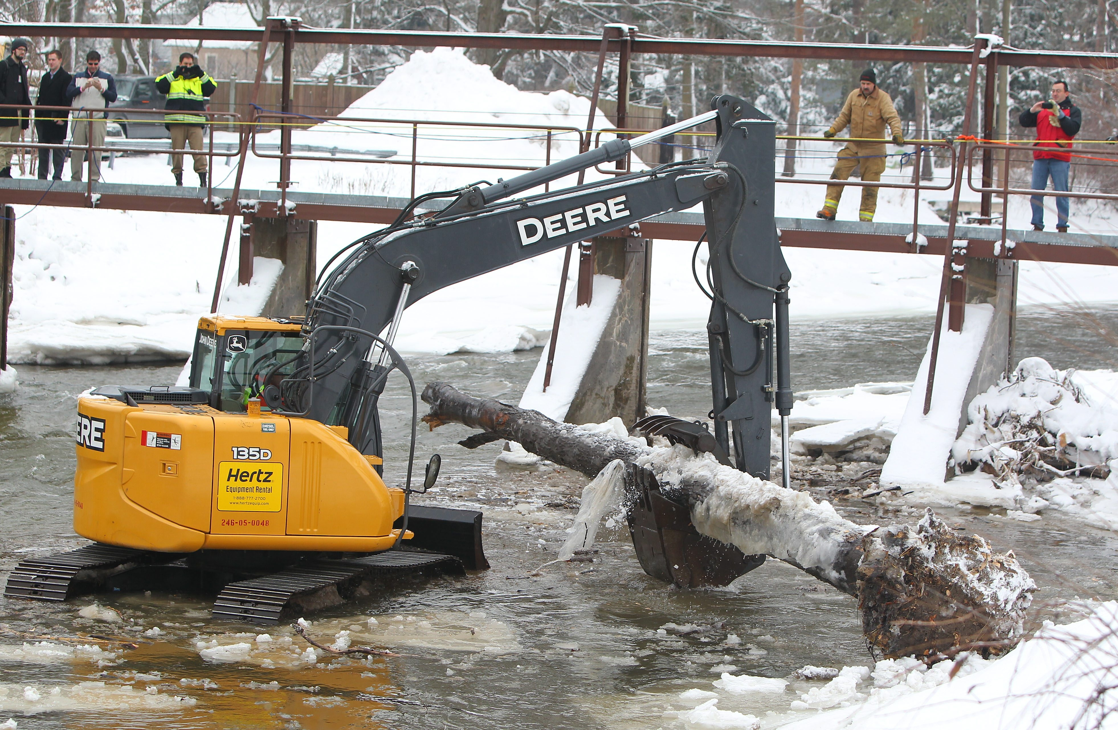 Ryan Maj, assistant public works crew chief in Williamsville, uses an excavator to remove debris from Ellicott Creek on Friday.