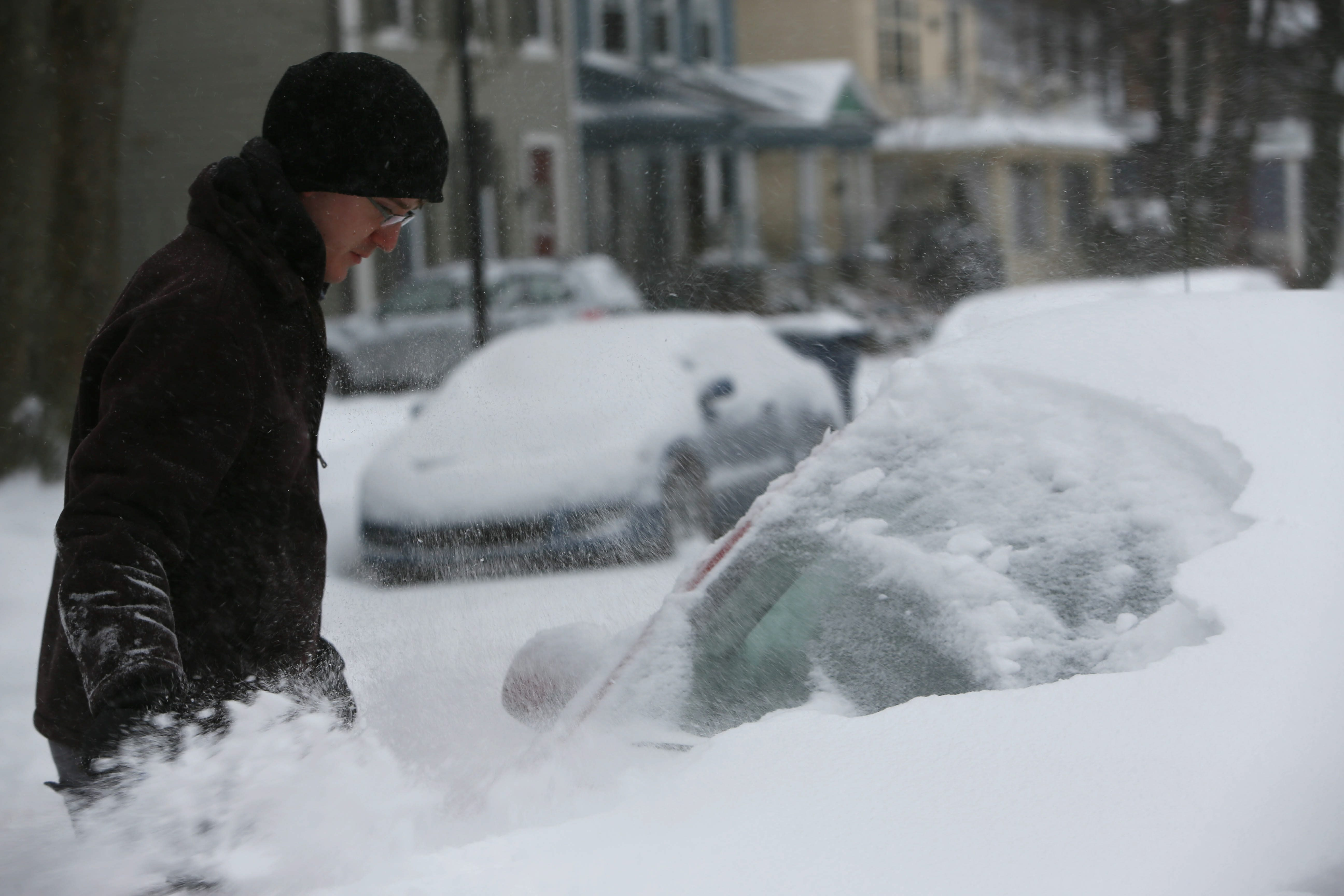Ryan Burdick clears snow off his car on Norwood Avenue earlier this month.