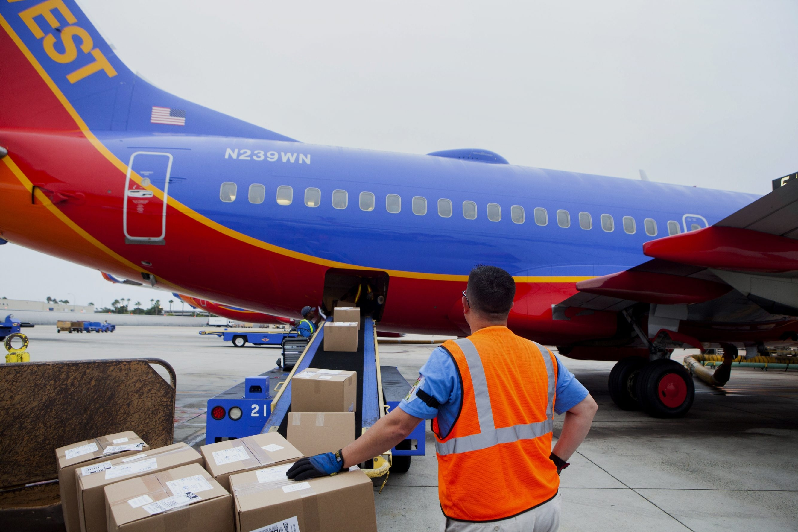 A ground crew member loads cargo onto a Southwest Airlines Co. Boeing Co. 737-7H4 airplane at San Diego International Airport in San Diego, Calif., on Sept. 19.