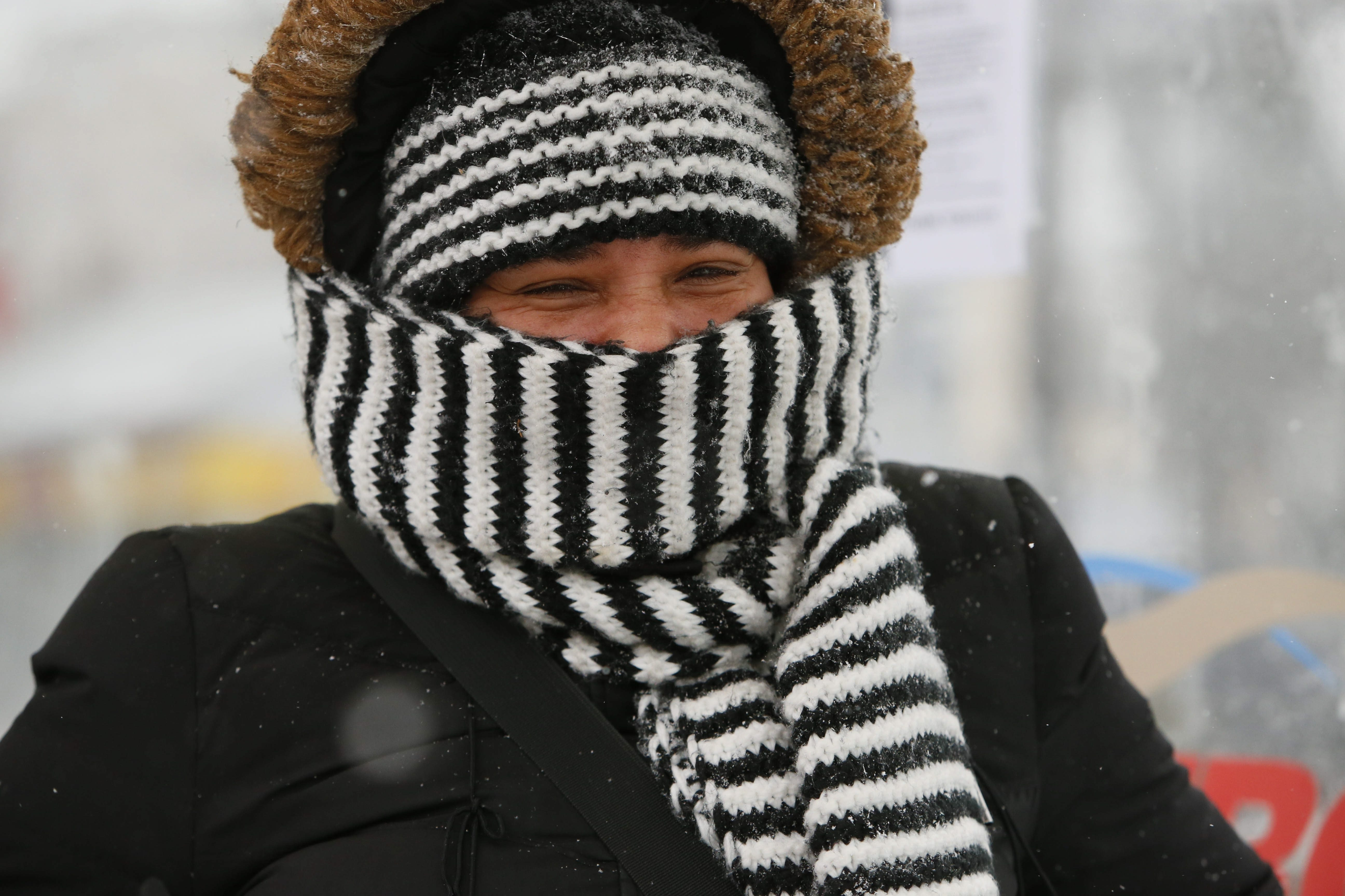 Tanya Ruffins of Buffalo is bundled up as she waits for a bus on Delaware Avenue on her way to work Monday.