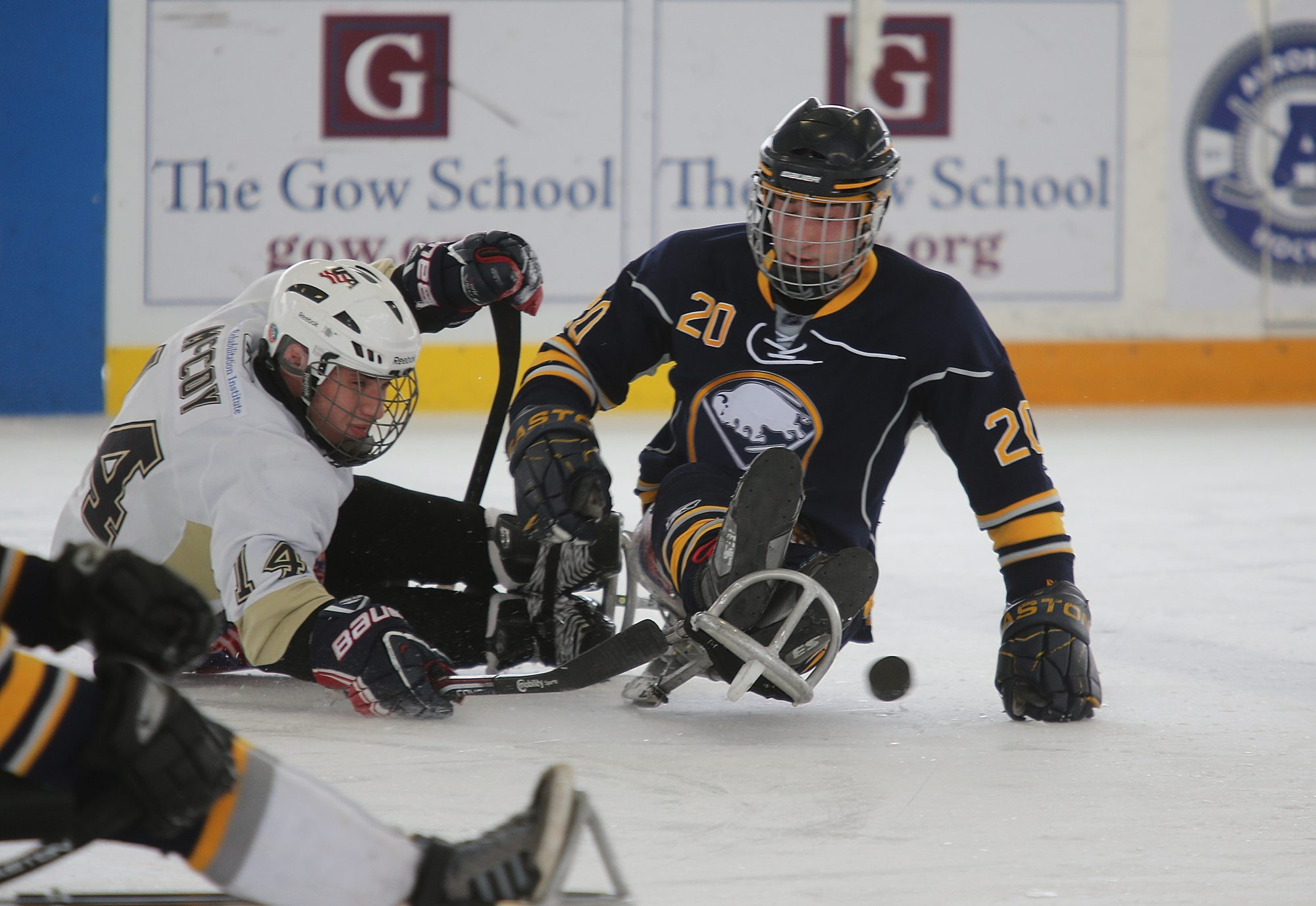 Buffalo sled hockey player Adam Page, of Lancaster, right, battles Pittsburgh player Dan McCoy, of Cheswick, Pa., for the puck Sunday at the Healthy Zone Ice Rink in East Aurora. The Sabres-sponsored team won, 7-3. Page – who scored six of his team's goals – also made the 2014 U.S. Paralympic Sled Hockey team.