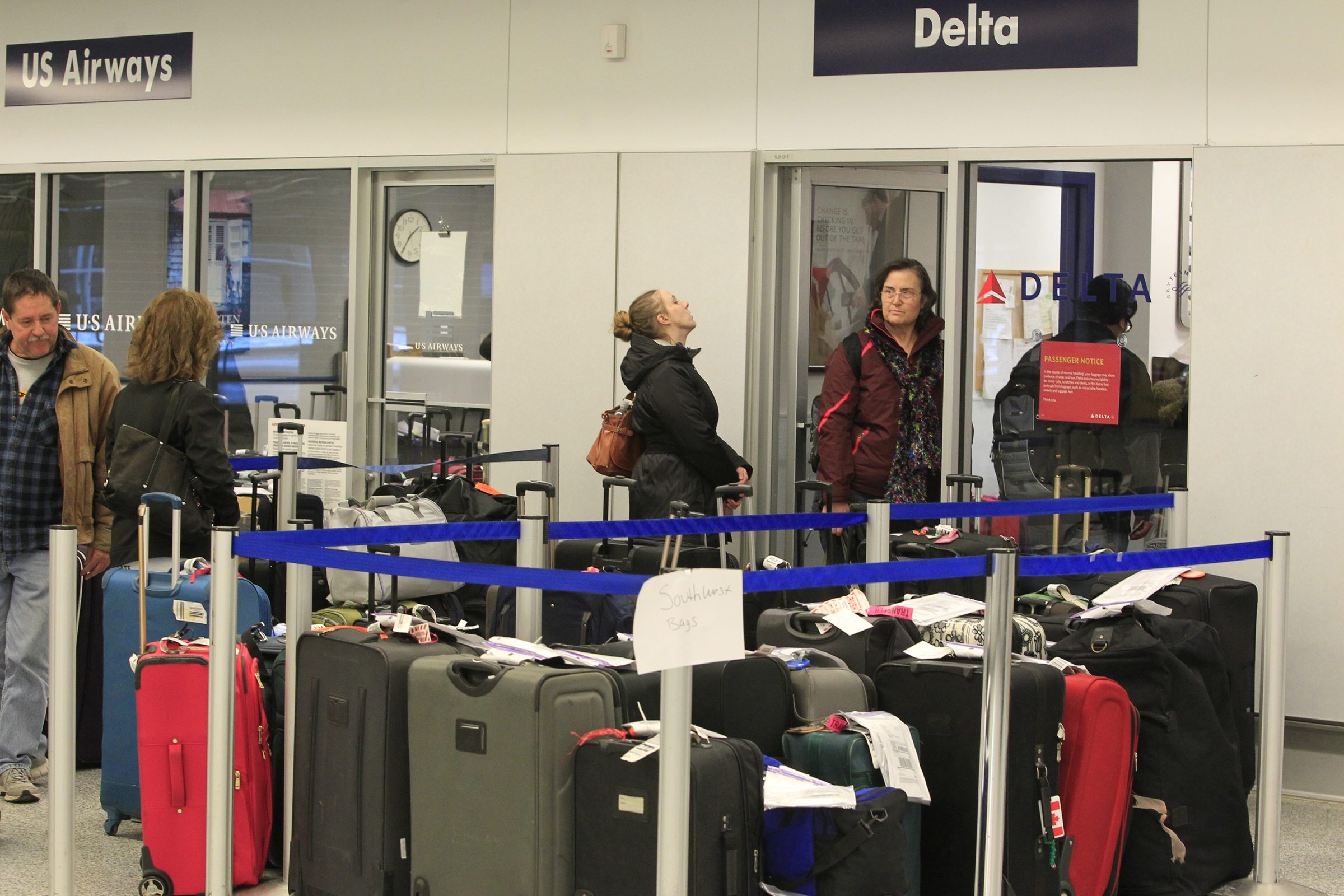 Passengers look for their luggage at the airport Monday, when at least 80 flights to and from Buffalo were cancelled.