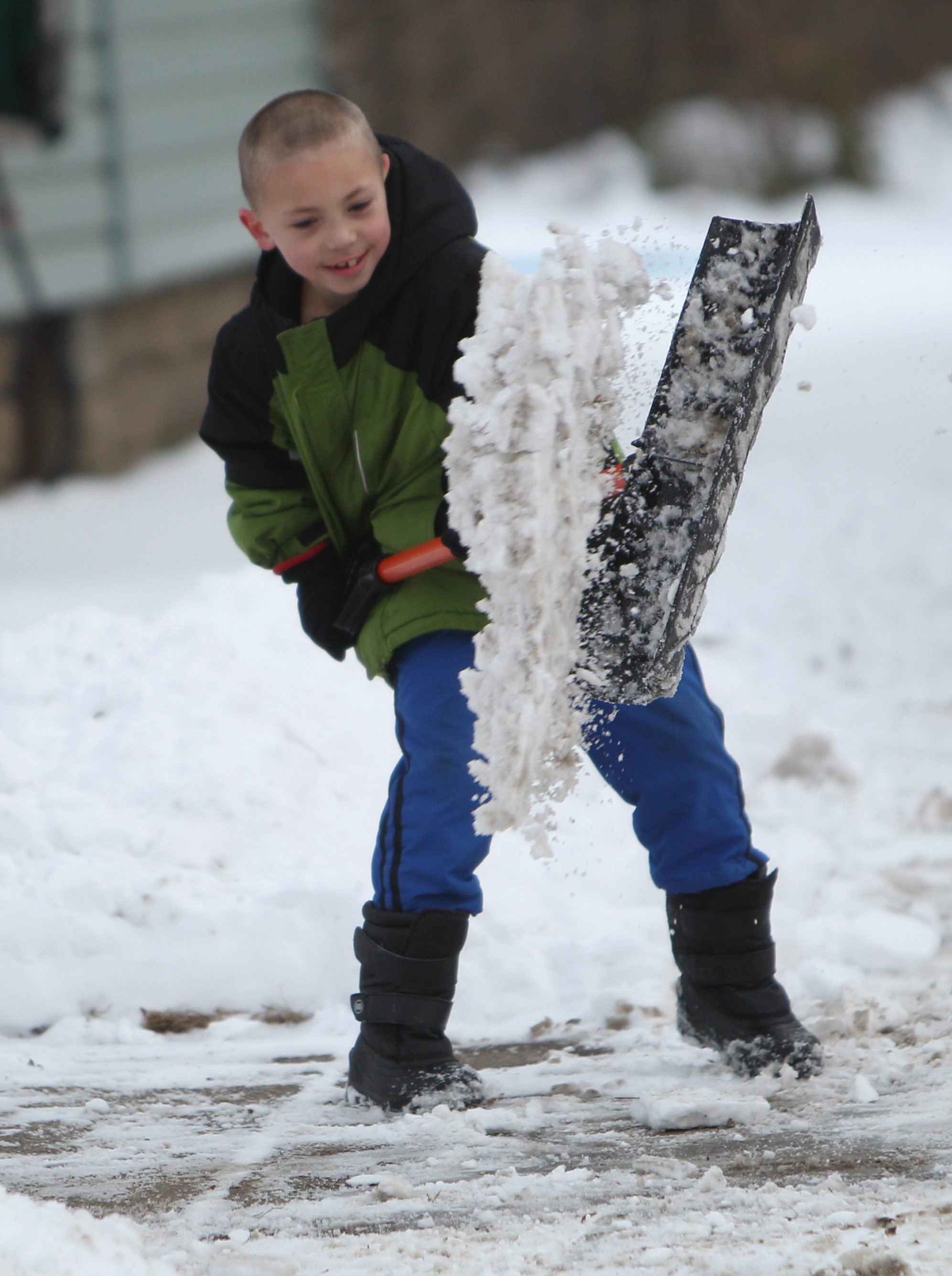 Jacob Hannahalon, 7, of Wheatfield Street in North Tonawanda, works hard at removing the packed snow from his driveway Saturday. He's likely to get more practice in the near future.