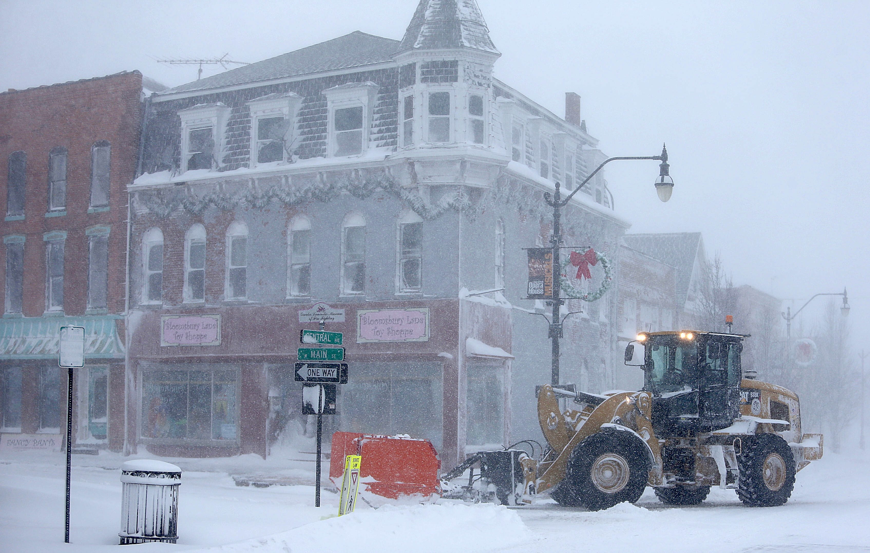 A large loader tries to keep the drifting snow at bay Tuesday on Central Avenue in the Village of Lancaster.