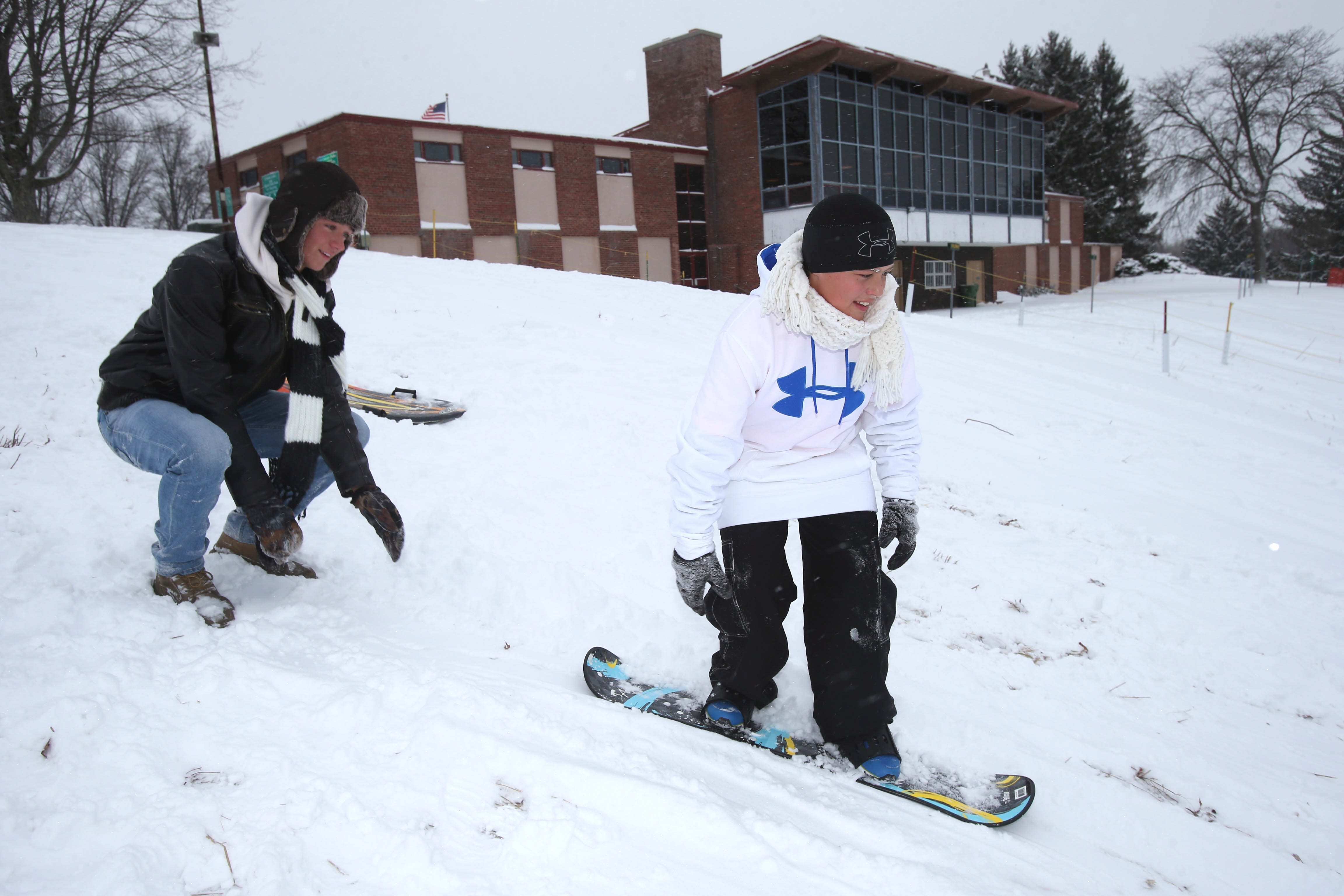 Mark Murr, 16, of Cheektowaga, pushes cousin Irvin Murr, 11, of Orlando, Fla., on his snowboard  Thursday at Elma Meadows County Park. County parks provide free winter activities.